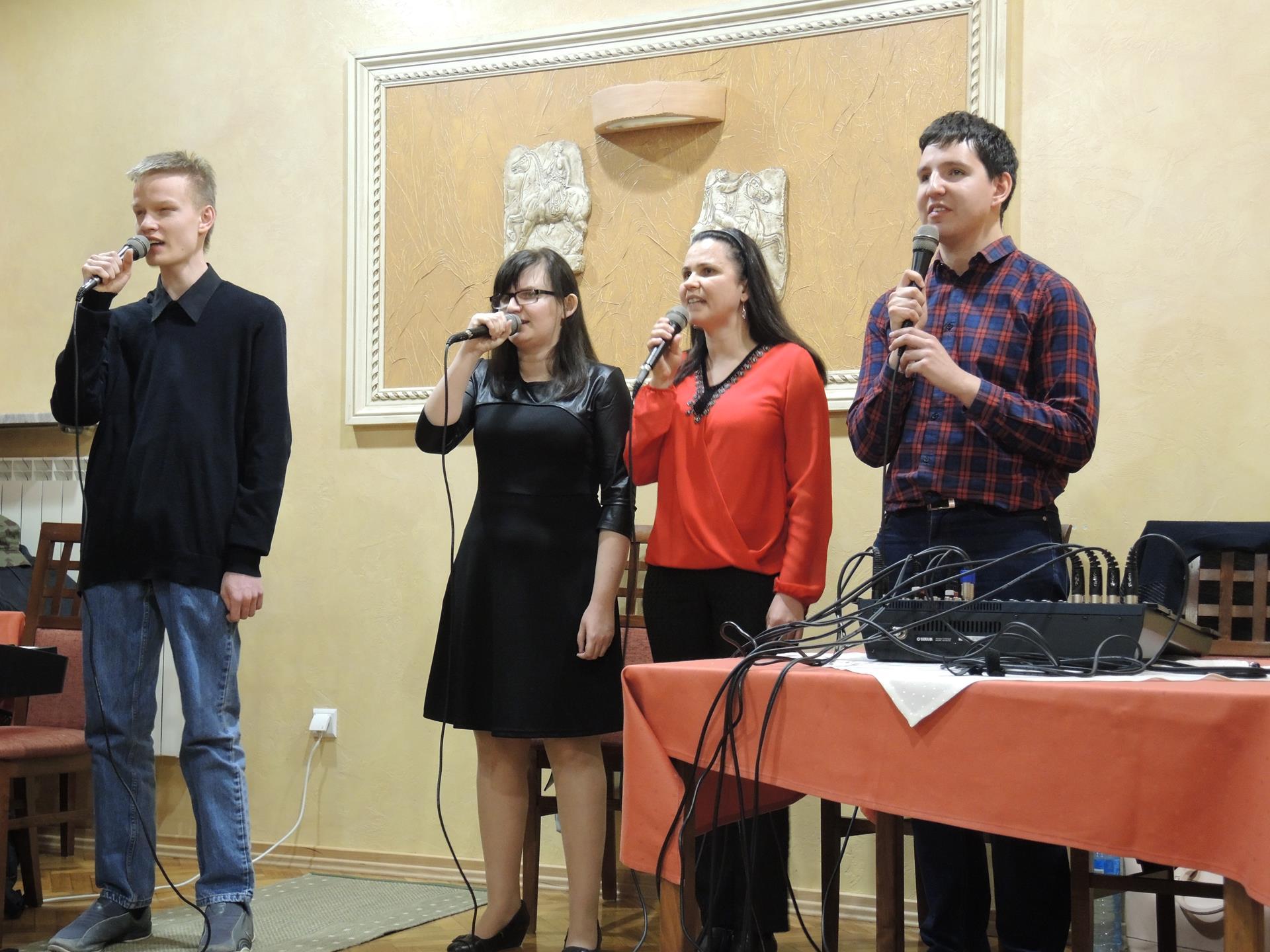 Dwie kobiety i dwóch mężczyzn śpiewa, w dłoniach trzymają mikrofony. Po prawej stronie stoi stół z mikserem.
