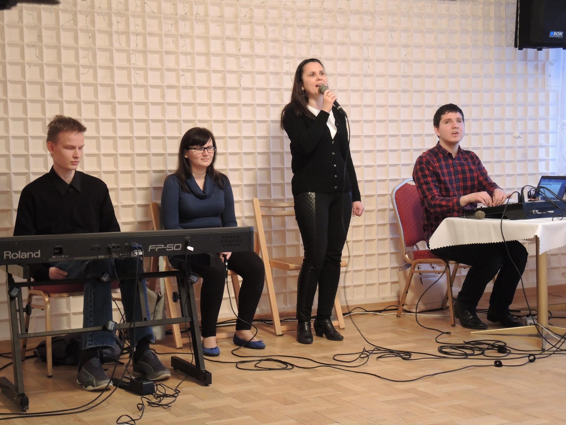 Kobieta stoi śpiewa, po jej prawej stronie siedzi kobieta i mężczyzna, mężczyzna ma przed sobą instrument klawiszowy. Po lewej stronie siedzi mężczyzna przy mikserze.