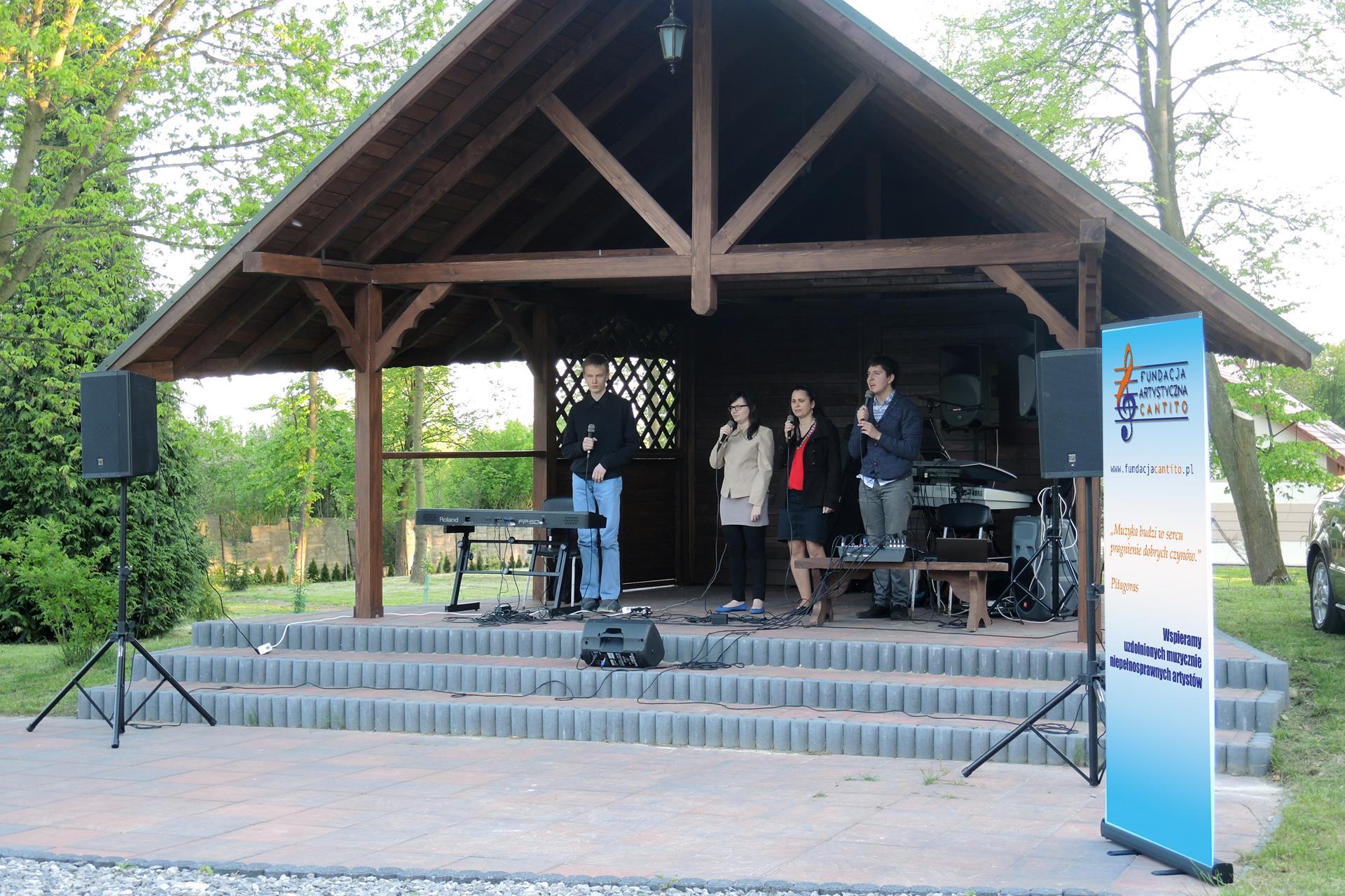 Pod drewnianą altaną śpiewają dwie kobiety i dwóch mężczyzn z mikrofonami w rękach. Przed mężczyzną stojącym po lewej stronie instrument klawiszowy, a obok drugiego mężczyzny z prawej strony mikser.