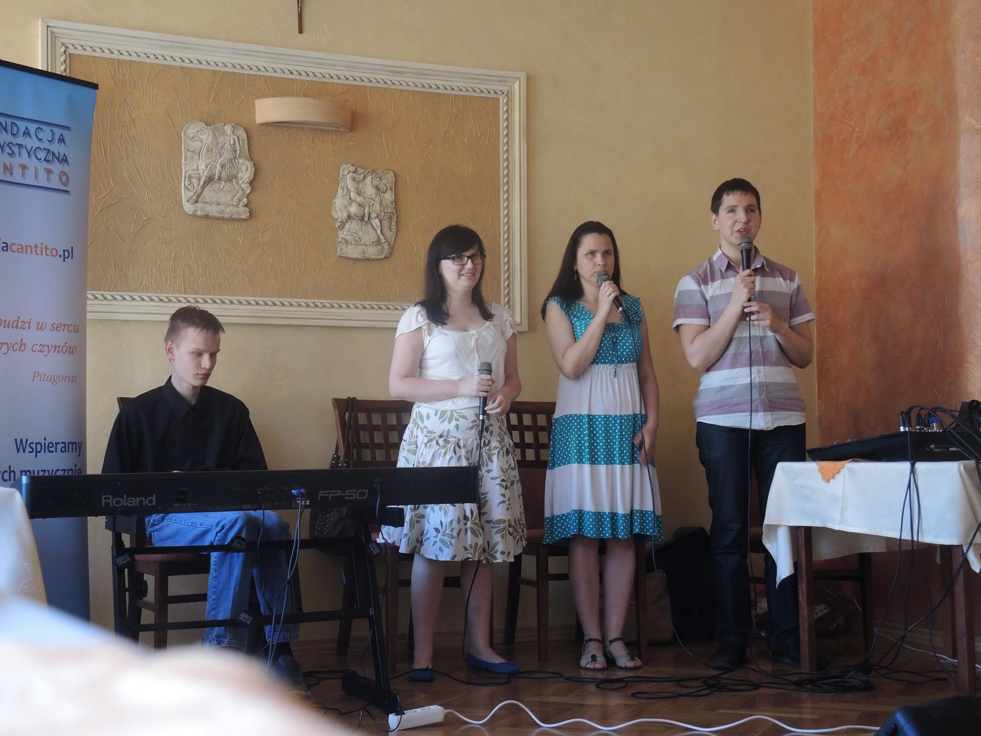 Trzy osoby (jeden mężczyzna, dwie kobiety) stoją, śpiewają. Po ich prawej stronie, przy klawiszach, siedzi mężczyzna. Po jego prawej stronie stoi fundacyjny rollup.