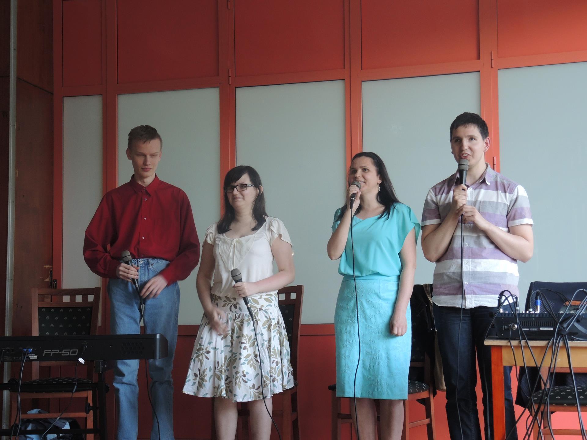 (cztery osoby - dwóch mężczyzn, wie kobiety) stoją, w rękach trzymają mikrofony. Mężczyzna i kobieta, którzy znajdują się na zdjęciu po prawej stronie, śpiewają.