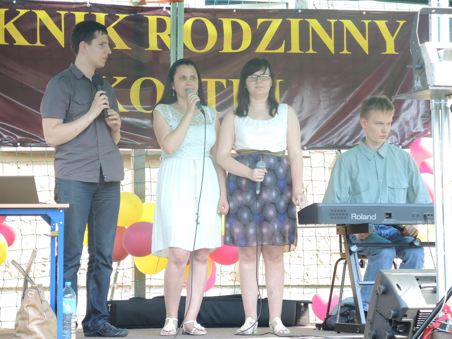 4 osoby stoją na scenie, kobieta przemawia, a 1 mężczyzna siedzi przy instrumencie klawiszowym