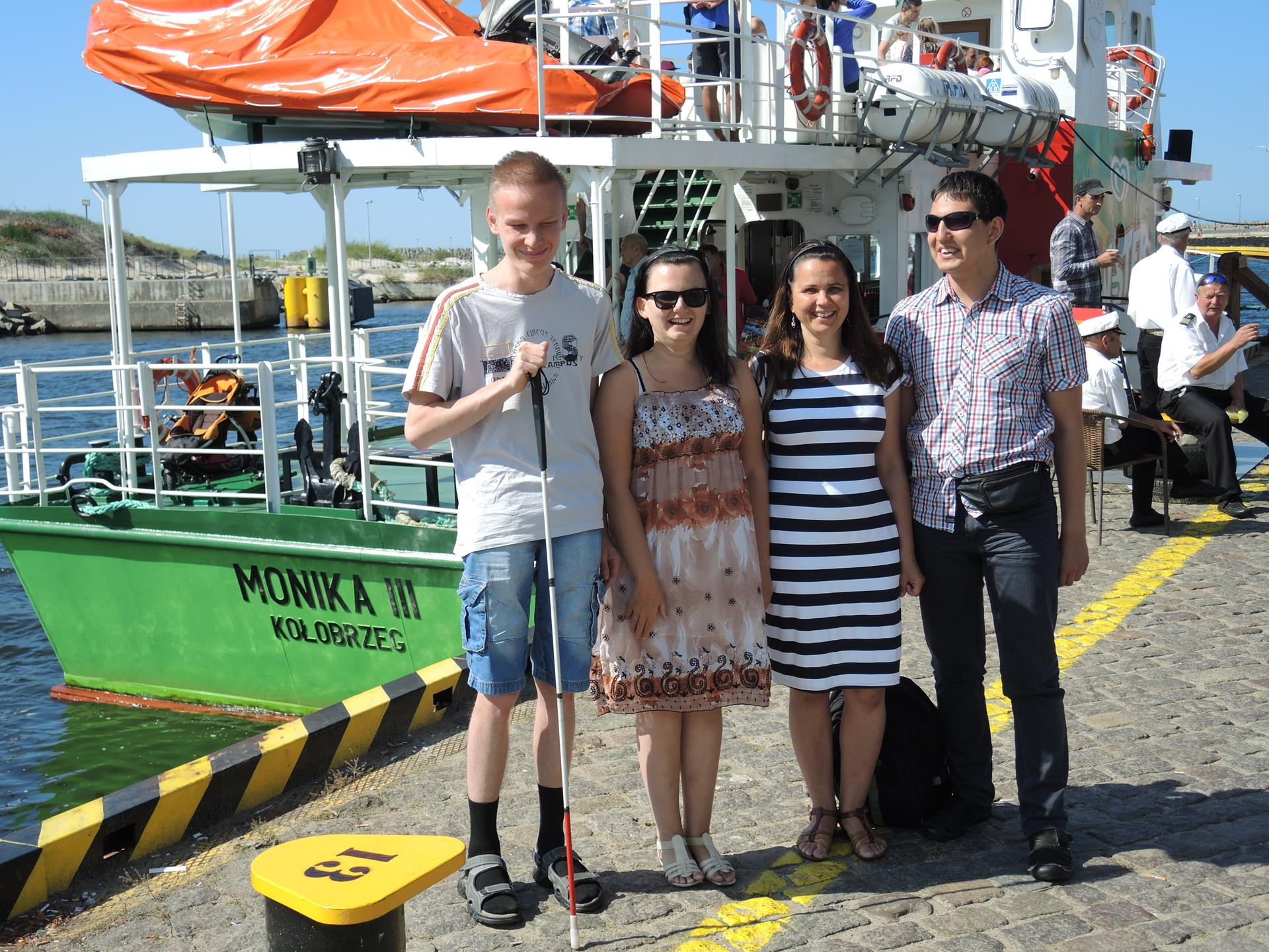 Cztery osoby (dwóch mężczyzn dwie kobiety) stoją na tle statku Monika III. Uśmiechają się.
