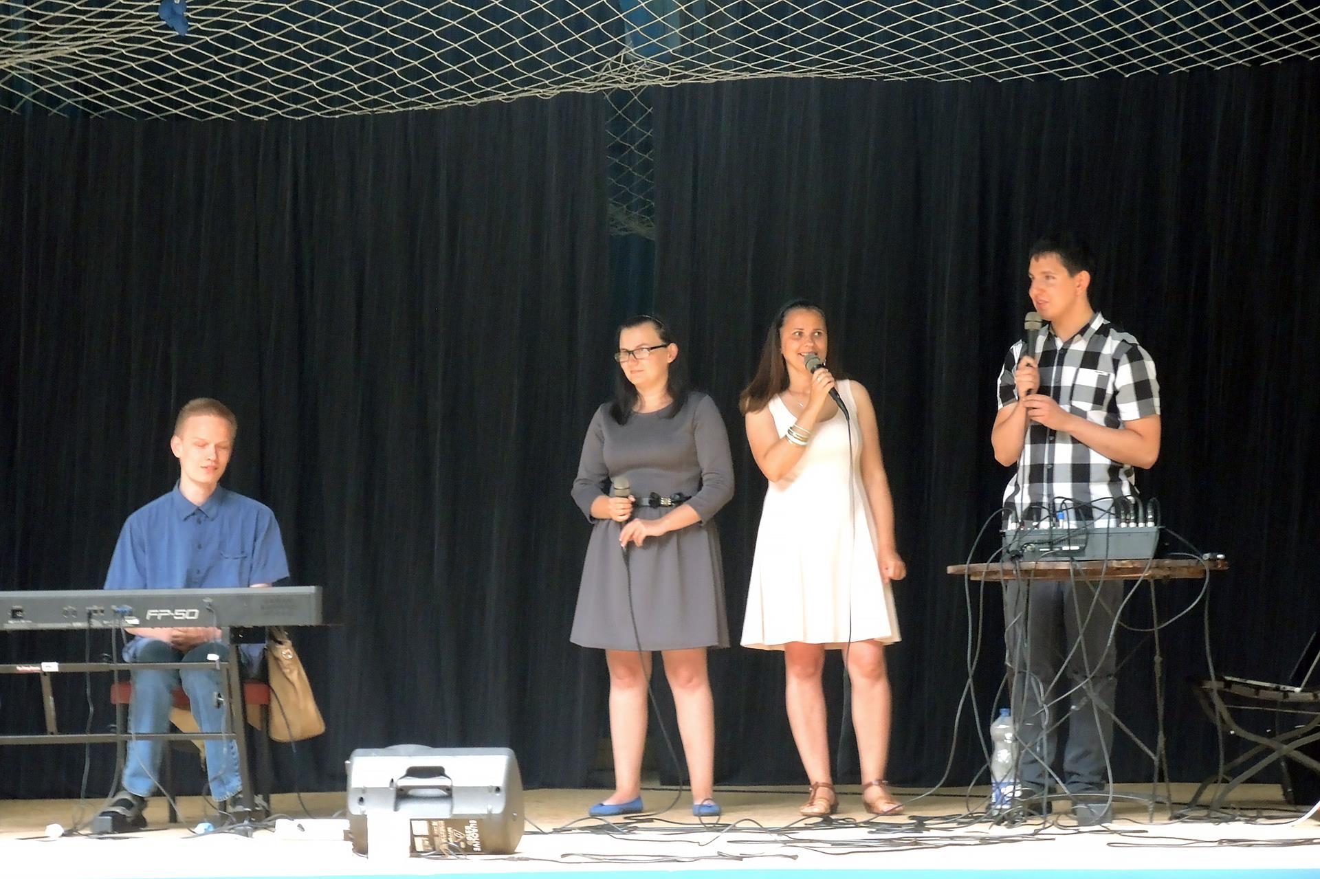 Cztery osoby stoją na scenie. Po prawej stronie, za klawiszami, siedzi mężczyzna po jego lewej stronie stoi kobieta w dłoniach trzyma mikrofon, obok niej stoi kobieta, która śpiewa, a po jej lewej stronie stoi mężczyzna, który trzyma w dłoniach mikrofon. Przed nim stoi stolik, na którym stoi mikser.