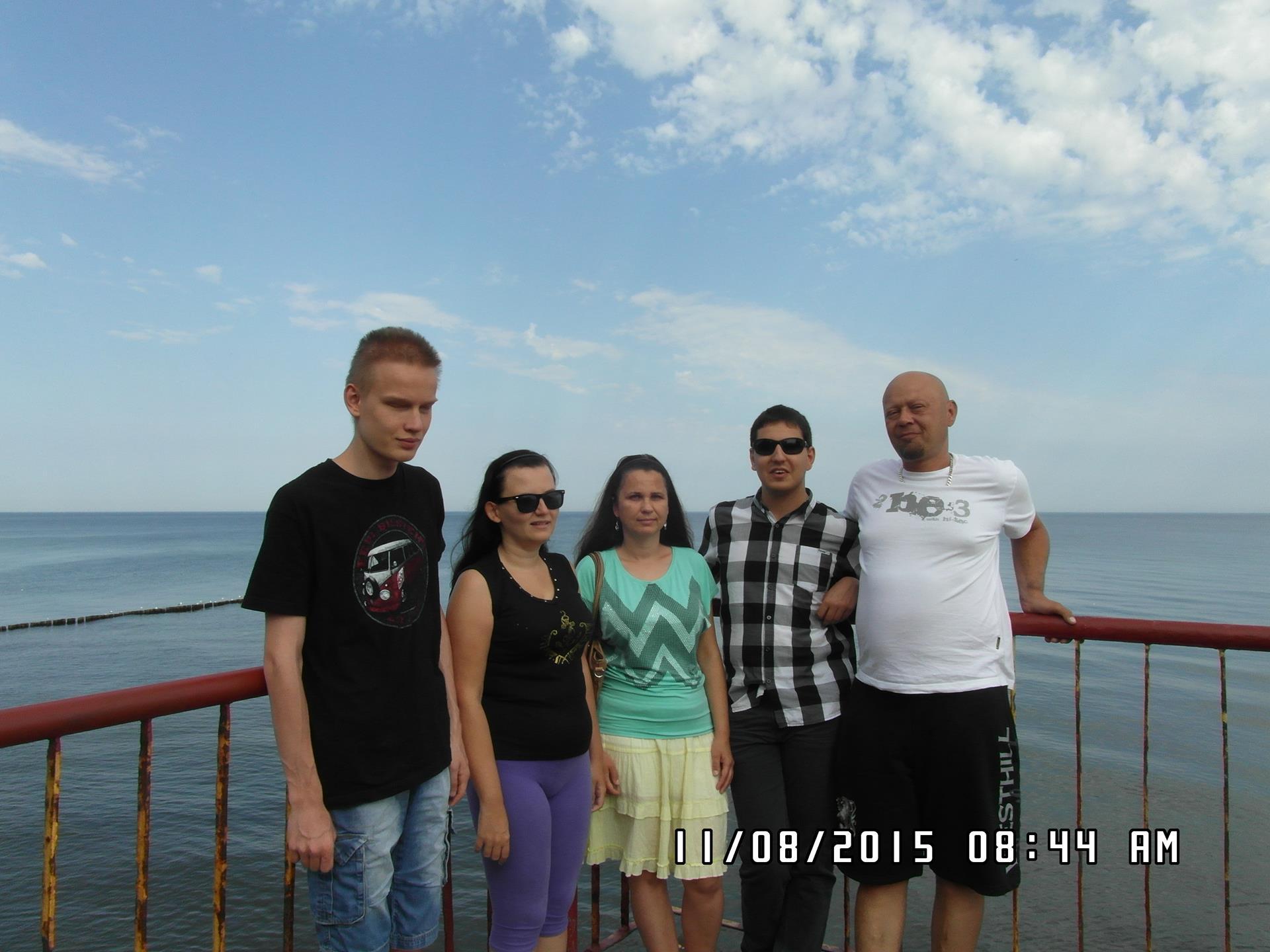 Pięć osób (trzech mężczyzn i dwie kobiety) stoi na molo. W tle widać morze.
