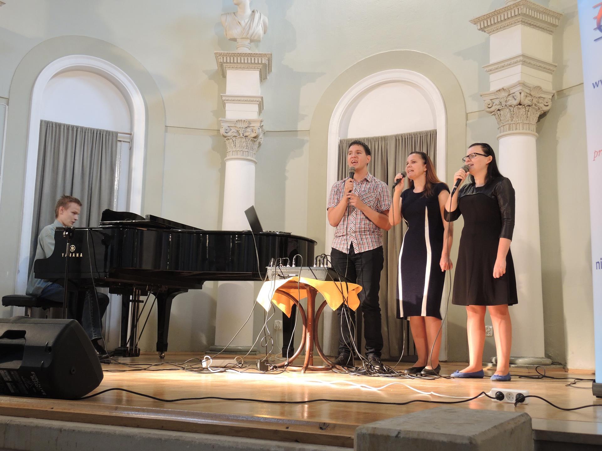 Mężczyzna gra na fotepianie. Obok stoją i śpiewają dwie kobiety i jeden mężczyzna.