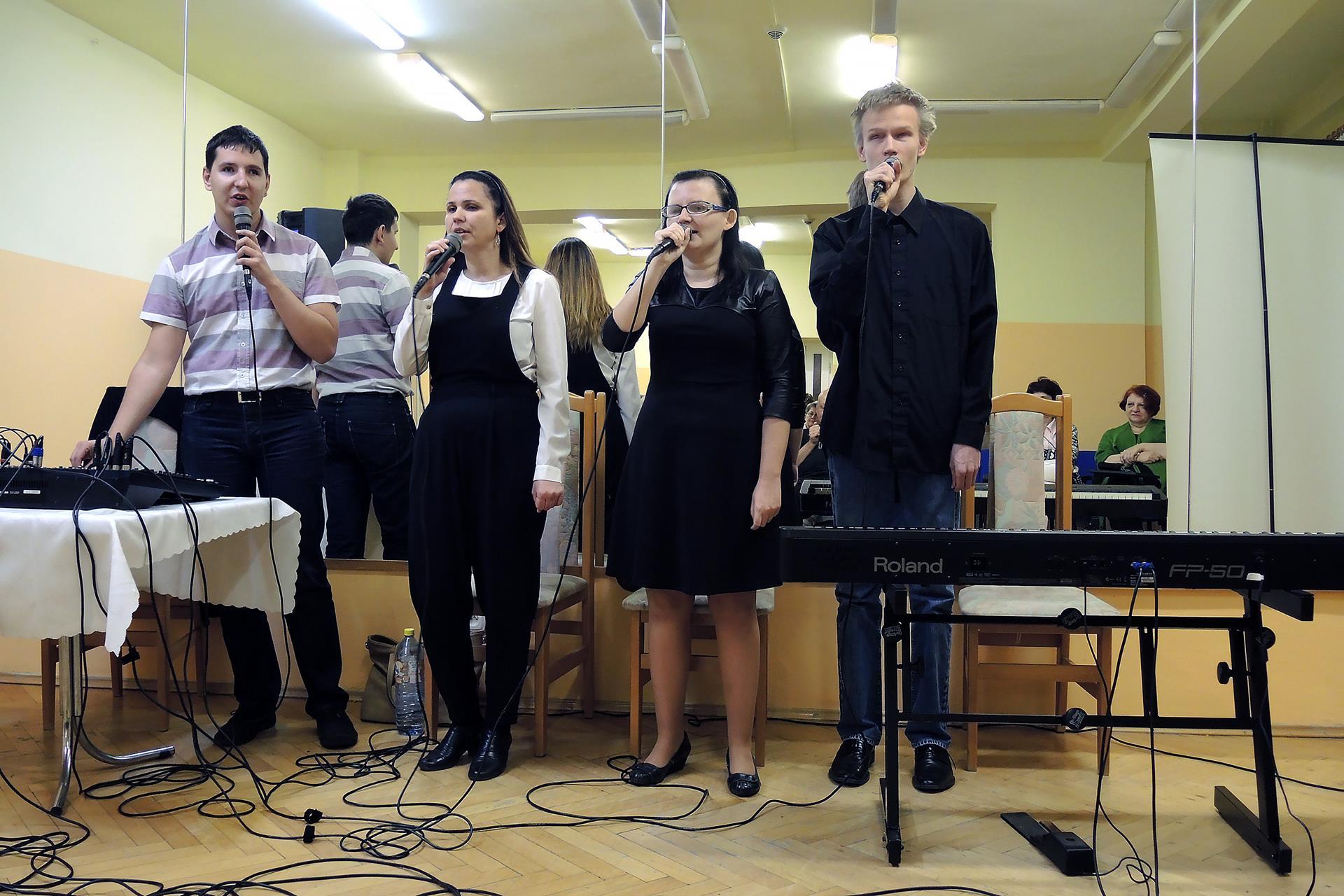 Cztery osoby (dwóch mężczyzn i dwie kobiety) stoją na tle ściany z luster, śpiewają. Przed mężczyzną, który stoi po prawej stronie stoi stolik a na nim mikser.  Przed mężczyzną, który stoi po lewej stoi statyw, a na nim klawisze. W odbiciu luster, które wiszą na ścianie widać kilka osób z publiczności.