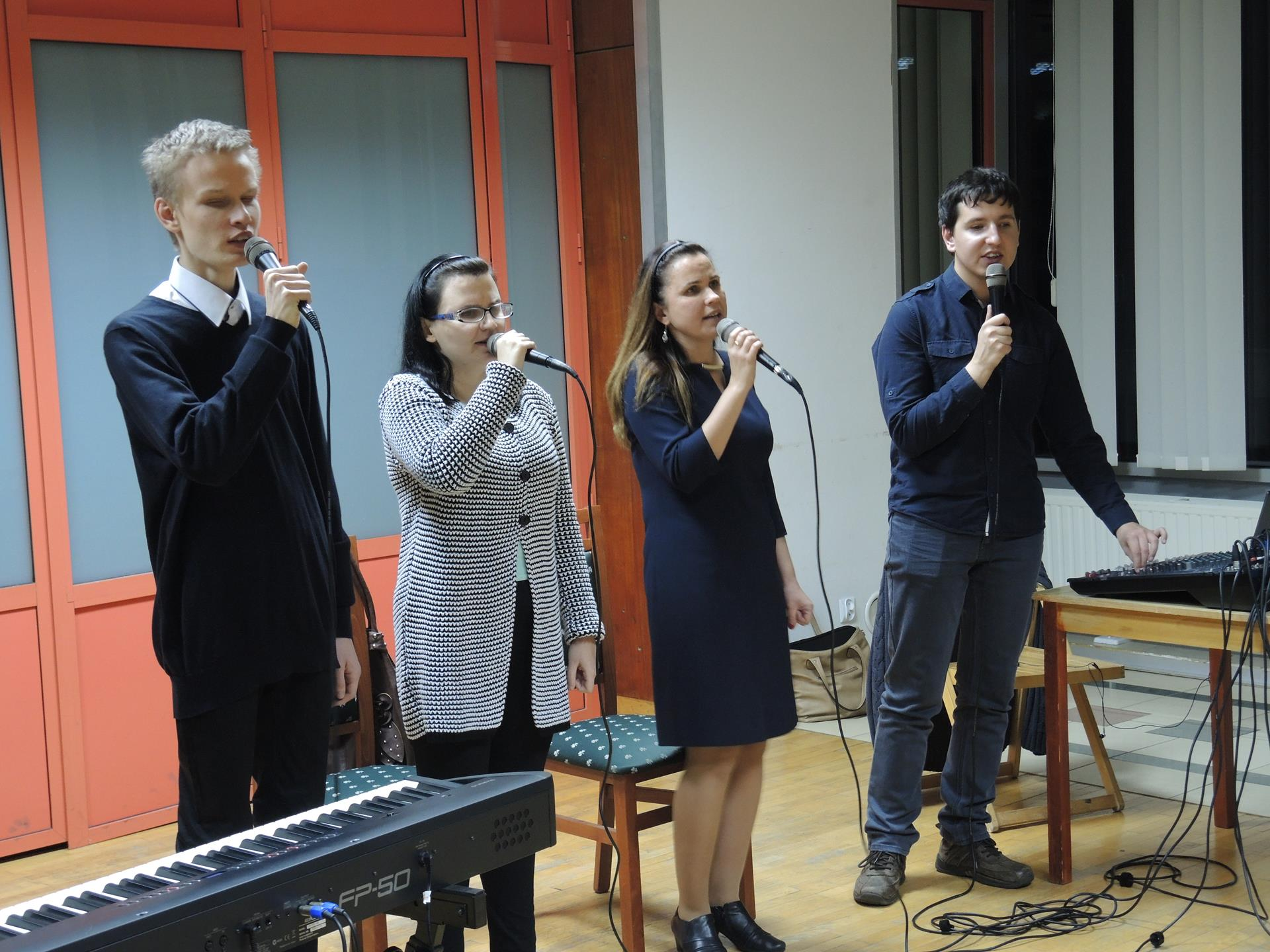 Cztery osoby (dwóch mężczyzn, dwie kobiety) stoją, śpiewają. Mężczyzna, który stoi po lewej stronie ma, po swojej prawej stronie, klawisze. Mężczyzna, który stoi po prawej ma przed sobą mikser.