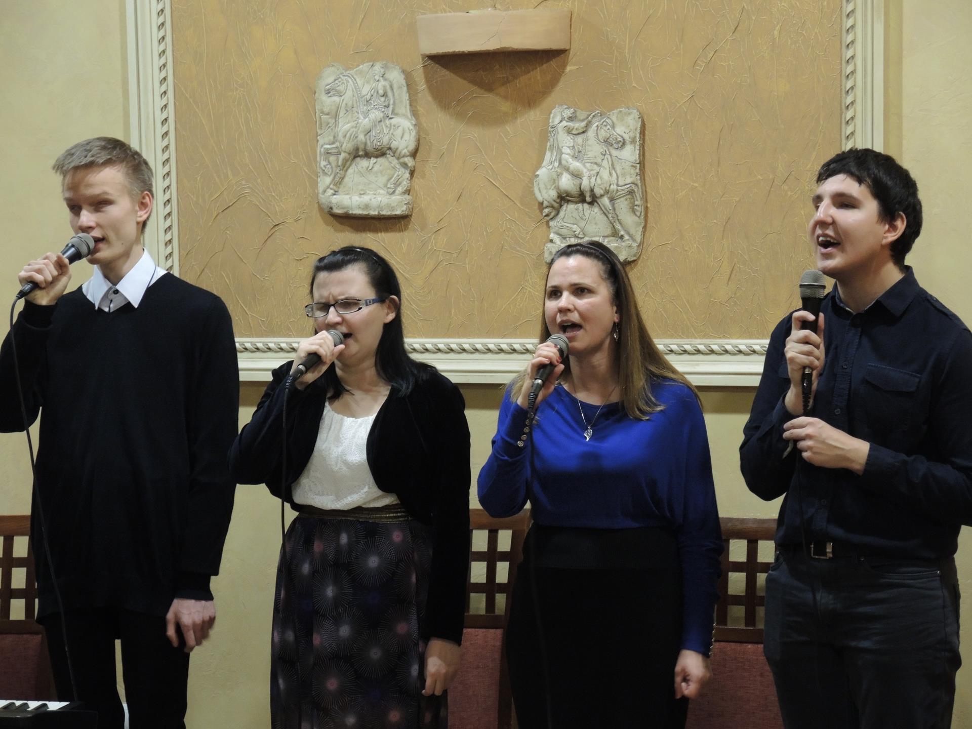 Wszyscy (dwóch mężczyzn, dwie kobiety) stoją, śpiewają. Na ścianie, na tle której stoją, wisi obraz.