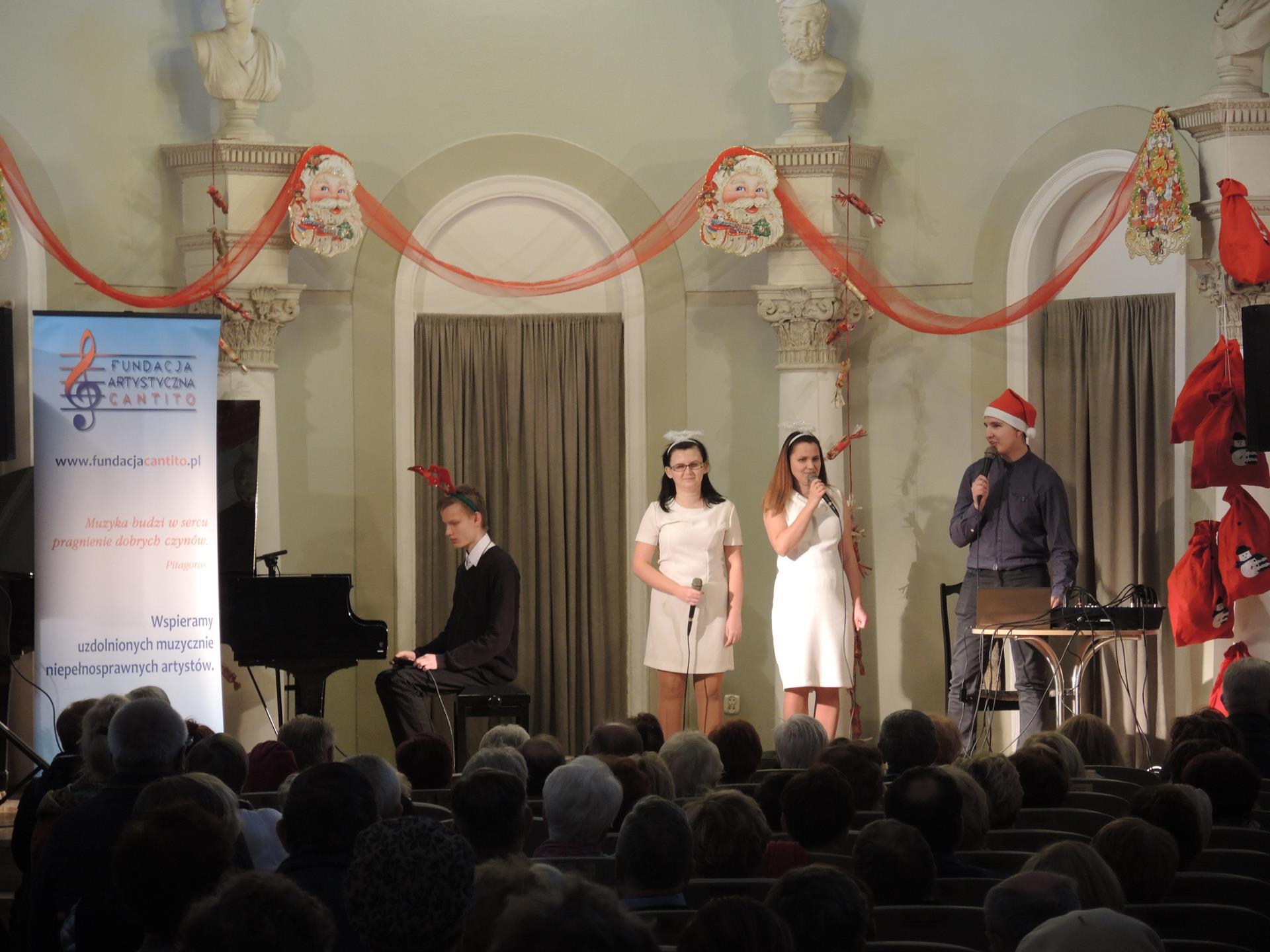 Scena widziana z oddalenia. Publiczność patrzy na scenę, na której znajdują  się cztery osoby – dwóch mężczyzn i dwie kobiety. Mężczyzna znajdujący się na scenie po lewej stronie siedzi przy fortepianie, pozostali stoją.  Występujący mają na sobie drobne mikołajowe akcenty.
