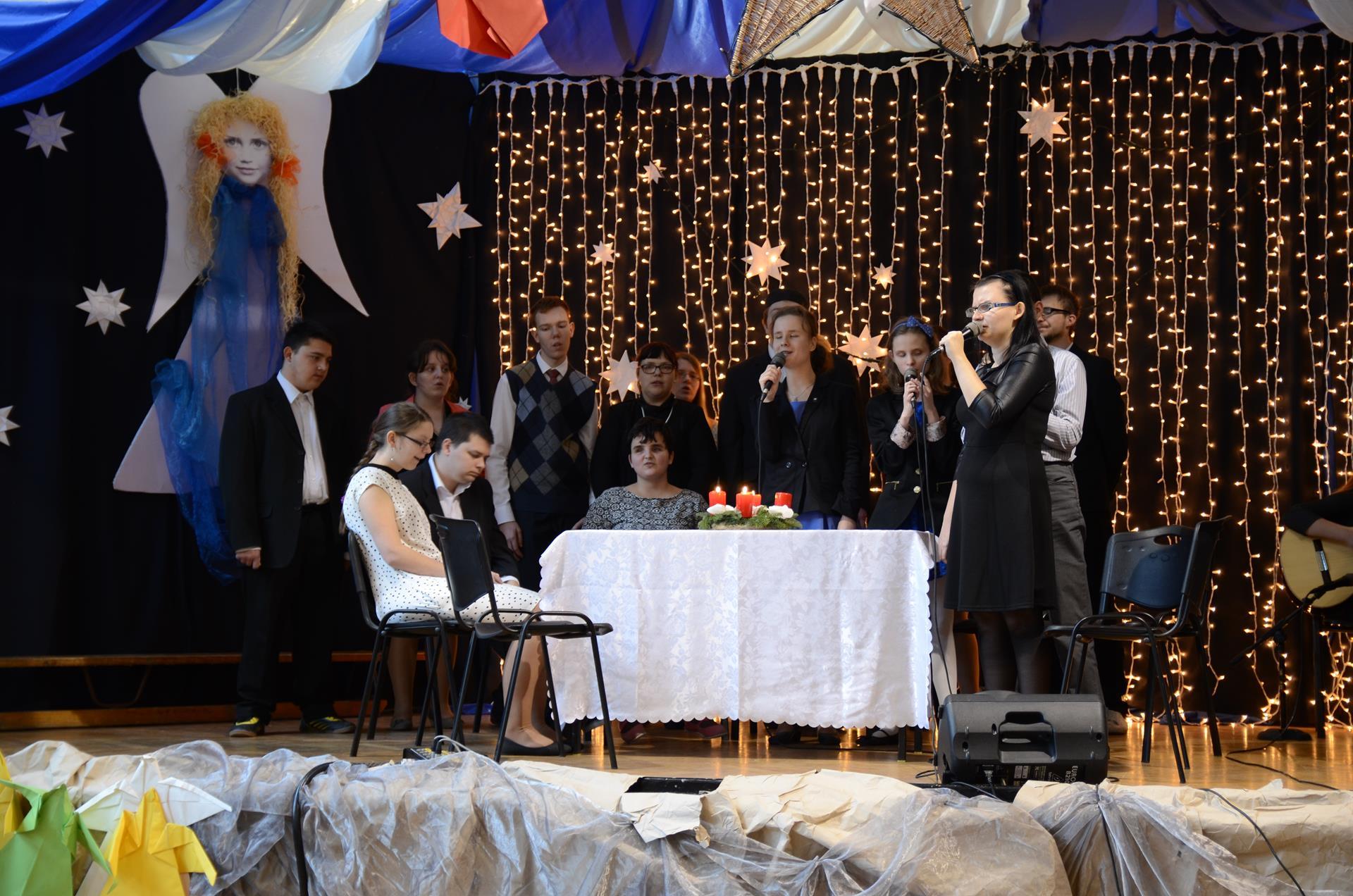 Na scenie znajduje się kilkanaście osób. Część z nich stoi, a część siedzi przy stole, na którym jest biały obróz oraz świąteczny stroik, w dłoniach trzymają mikrofony. Scena jest przystrojona światełkami, białymi gwiazdkami i niebiesko-białym materiałem.