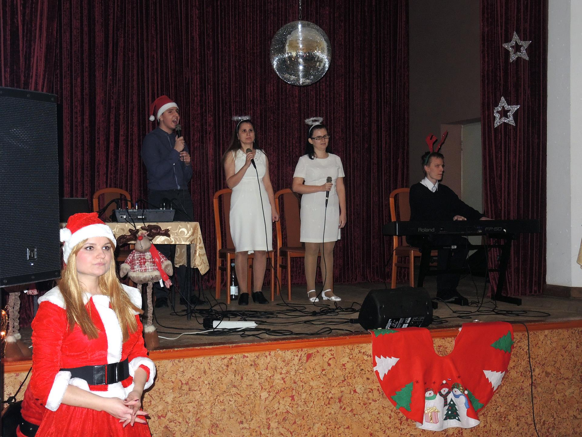 Na scenie znajdują się  cztery osoby – dwóch mężczyzn, dwie kobiety. Mężczyzna znajdujący się na scenie po prawej stronie gra na klawiszach, pozostali stoją, trzymają w dłoniach mikrofony. Wszyscy mają na sobie drobne akcenty mikołajowe. Pod sceną stoi pani, która jest przebrana za Mikołajkę.