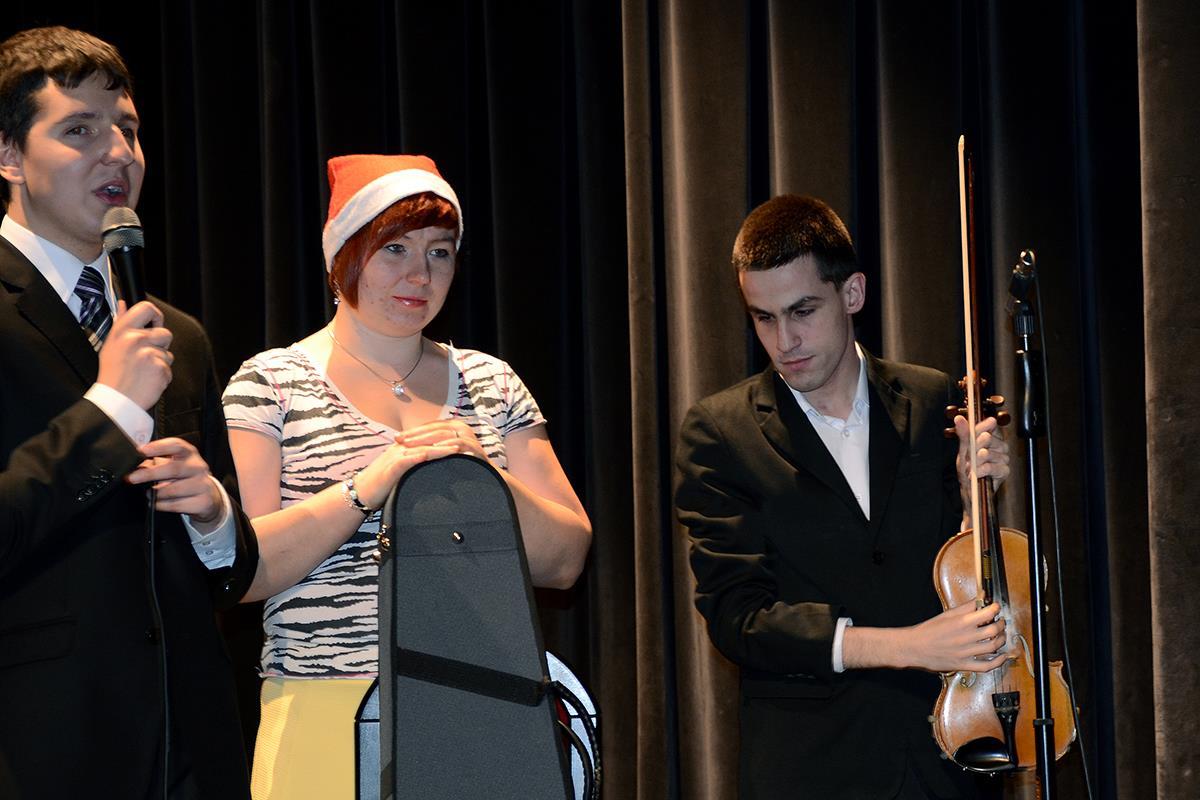 Kobieta stoi, na głowie ma czapkę mikołajową. Po jej lewej stronie stoi mężczyzna, który w dłoniach trzyma skrzypce. Po jej prawej stronie stroi mężczyzna, który w dłoniach trzyma mikrofon.