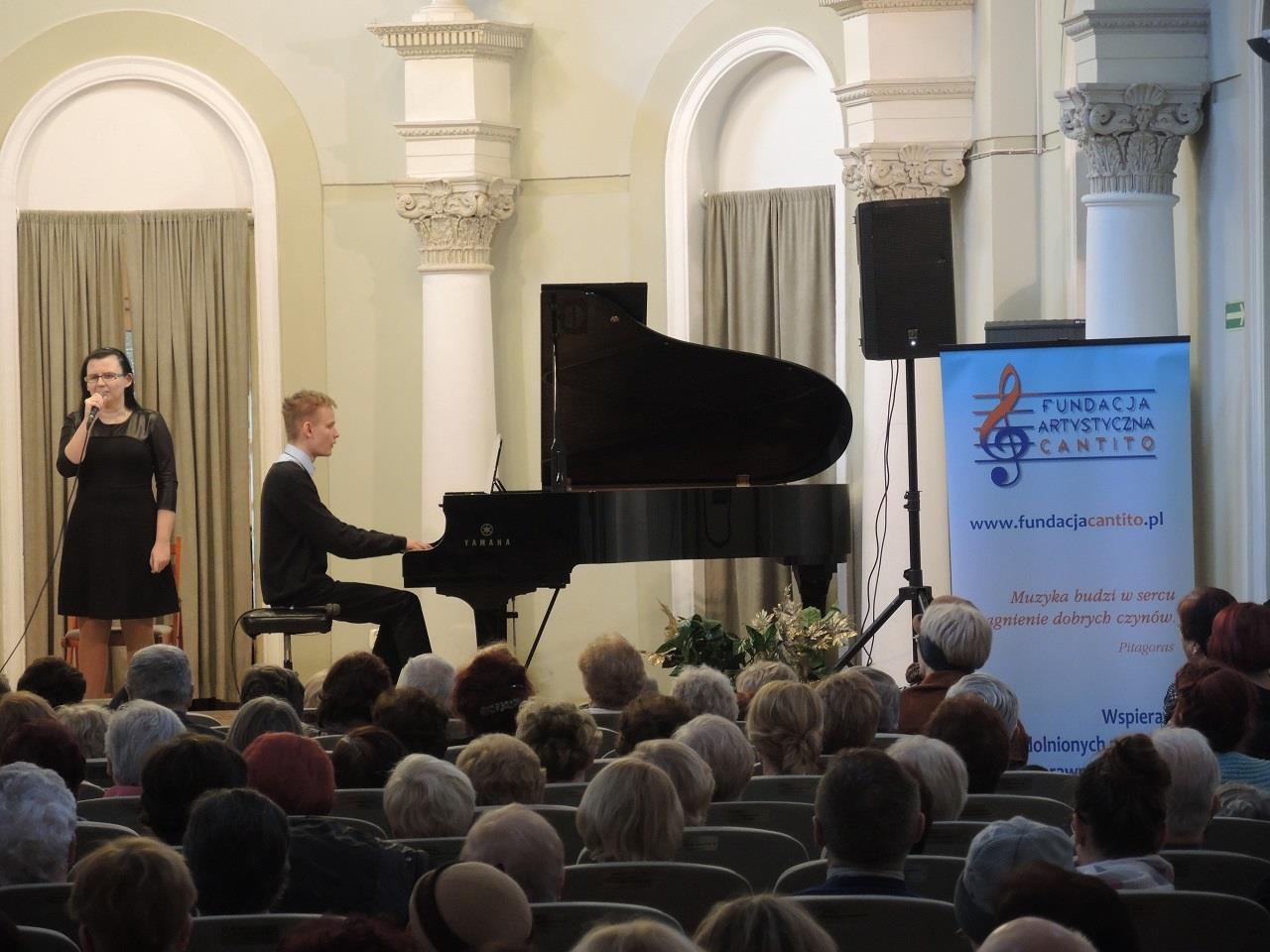 Zdjęcie z oddali. Kobieta stoi na scenie, śpiewa. Po jej lewej stronie siedzi mężczyzna, który gra na fortepianie. Patrzy na nich licznie przybyła publiczność.