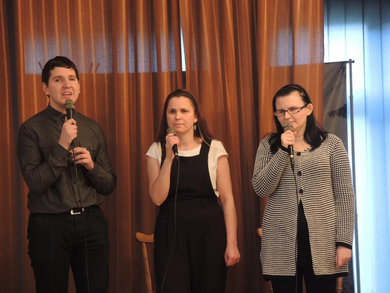 Mężczyzna śpiewa, po jego lewej stronie stoją dwie kobiety w dłoniach trzymają mikrofony.