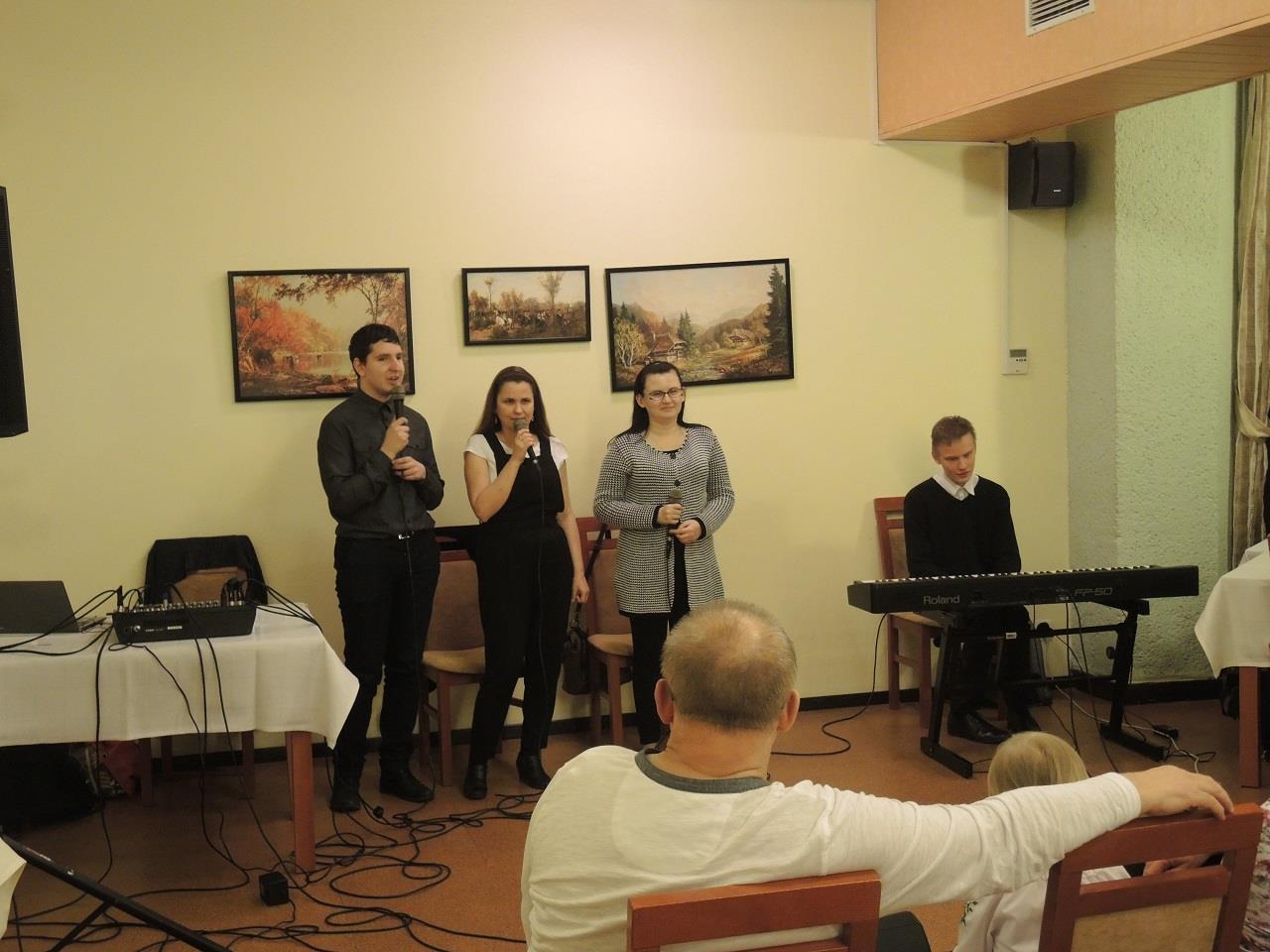 Trzy osoby (jeden mężczyzna i dwie kobiety) stoją, w dłonach trzymają mikrofony. Po ich lewej stronie siedzi mężczyzna, który ma przed sobą klawisze.