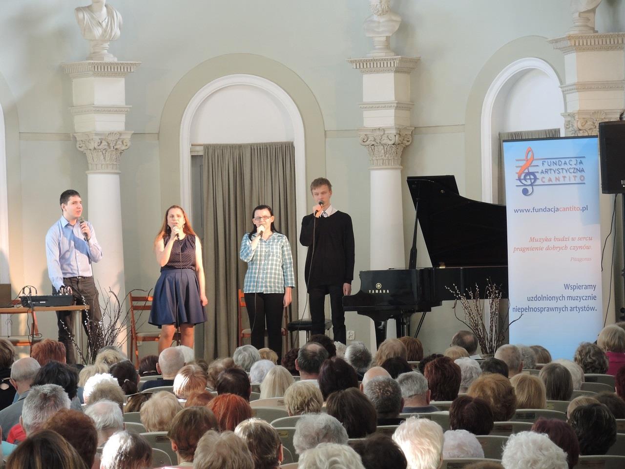 Zdjęcie zrobione z oddali. Licznie przybyła publiczność patrzy na scenę, na której znajdują się cztery osoby - dwóch mężczyzn i dwie kobiety. Wszyscy znajdujący się na scenie stoją, śpiewają.