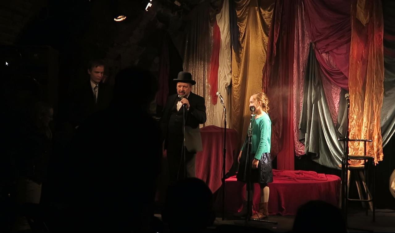 Na scenie stoją trzy osoby. Dwóch mężczyzn i dziewczynka.