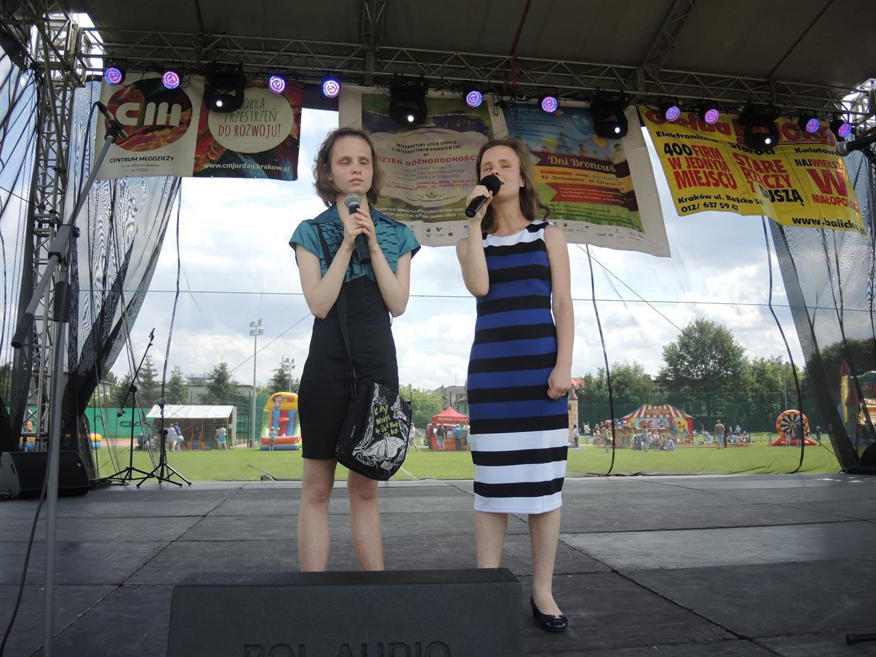 Na dużej scenie stoi Danusia i Natalia. Ubrane są w sukienki.