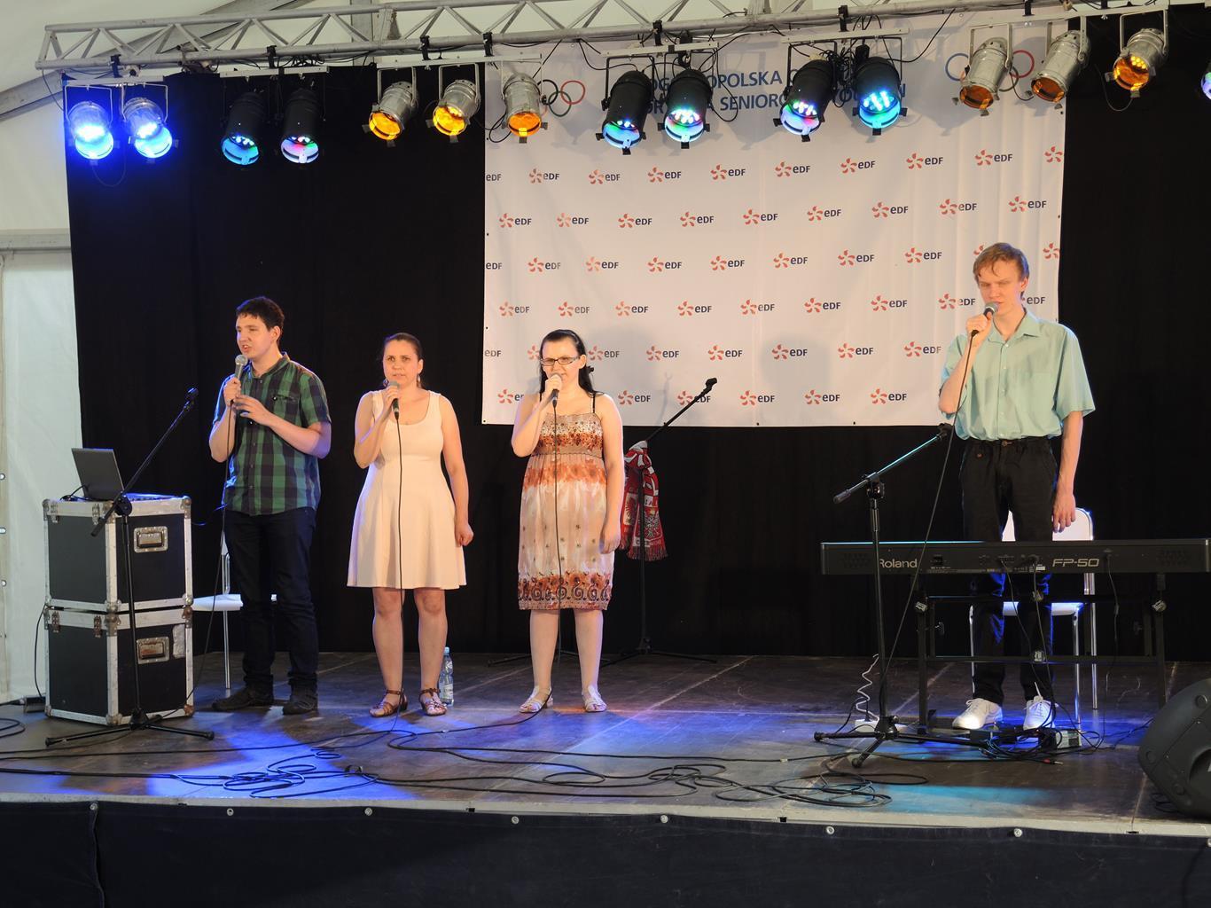 Cztery osoby stoją na scenie pod namiotem (dwie kobiety, dwóch mężczyzn) śpiewają.