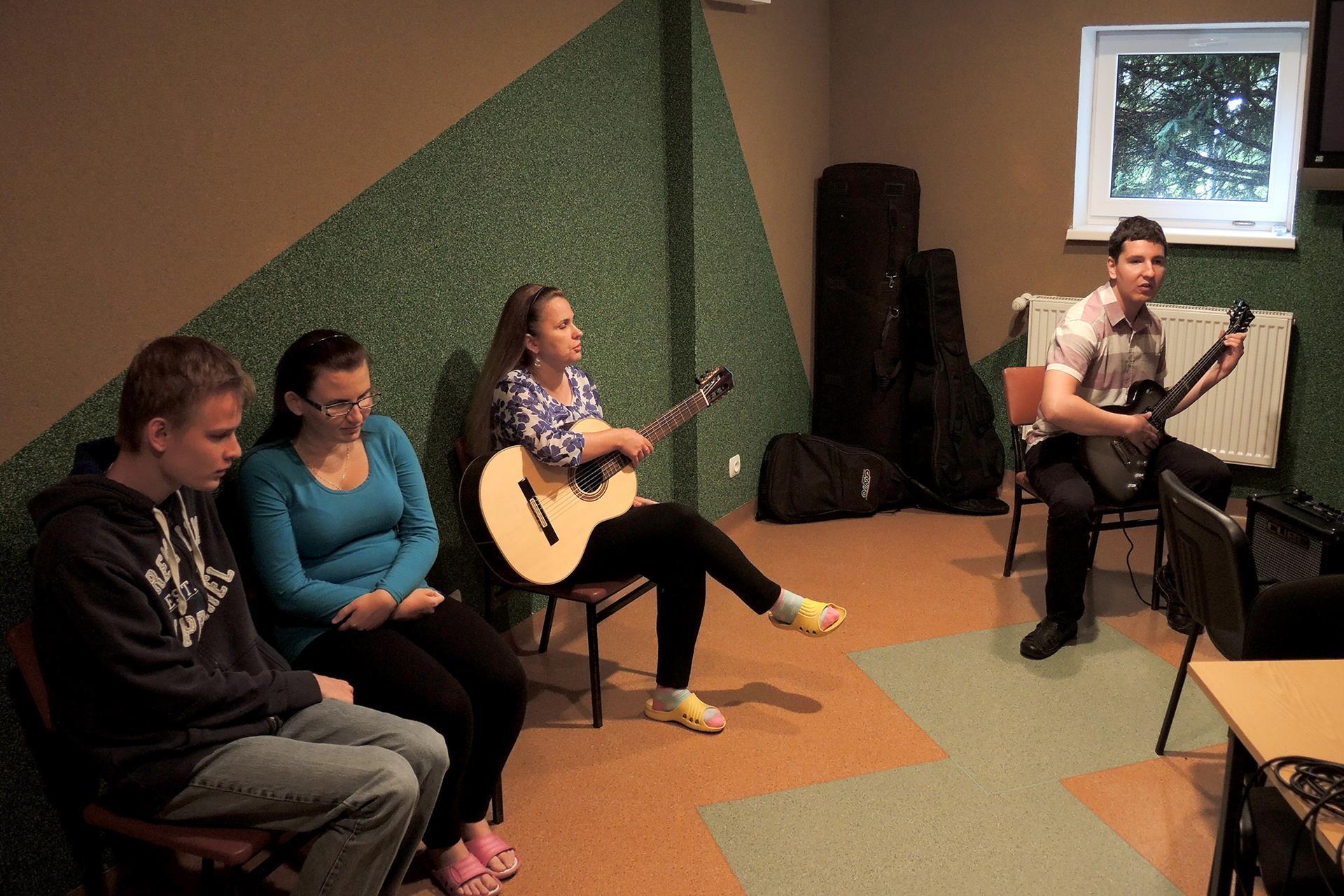 Mężczyzna gra na gitarze, obok niego siedzą dwie kobiety i mężczyzna.