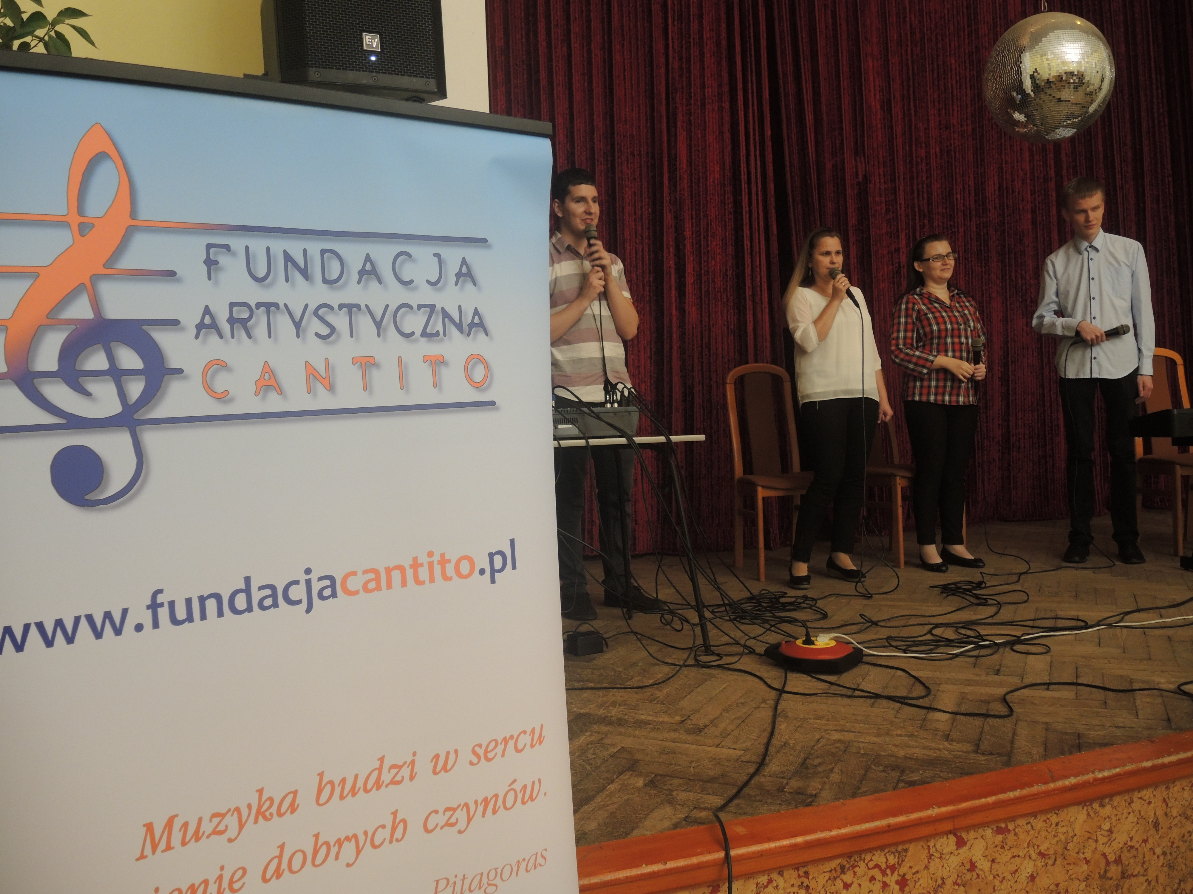 Cztery osoby (dwóch mężczyzn, dwie kobiety) stoją na scenie, uśmiechają się, w dłoniach trzymają mikrofony. Pod sceną, po prawej stronie, stoi roll up fundacji.