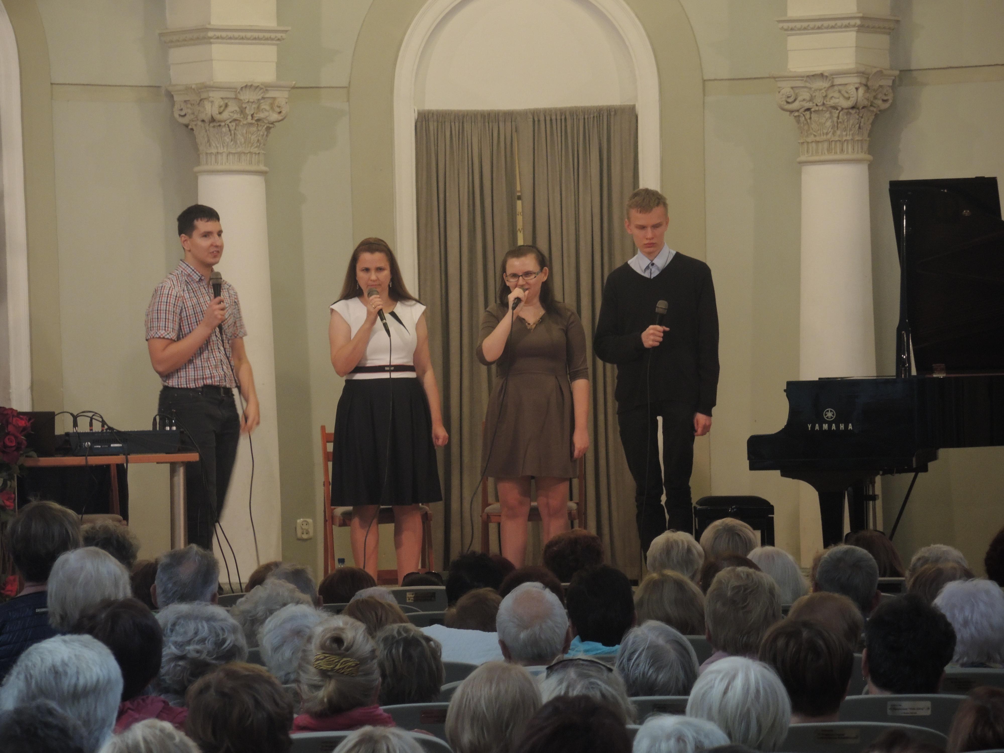 Zdjęcie zrobione z oddali. Cztery osoby (dwie kobiety i dwóch mężczyzna) stoją na scenie. W dłoniach trzymają mikrofony.