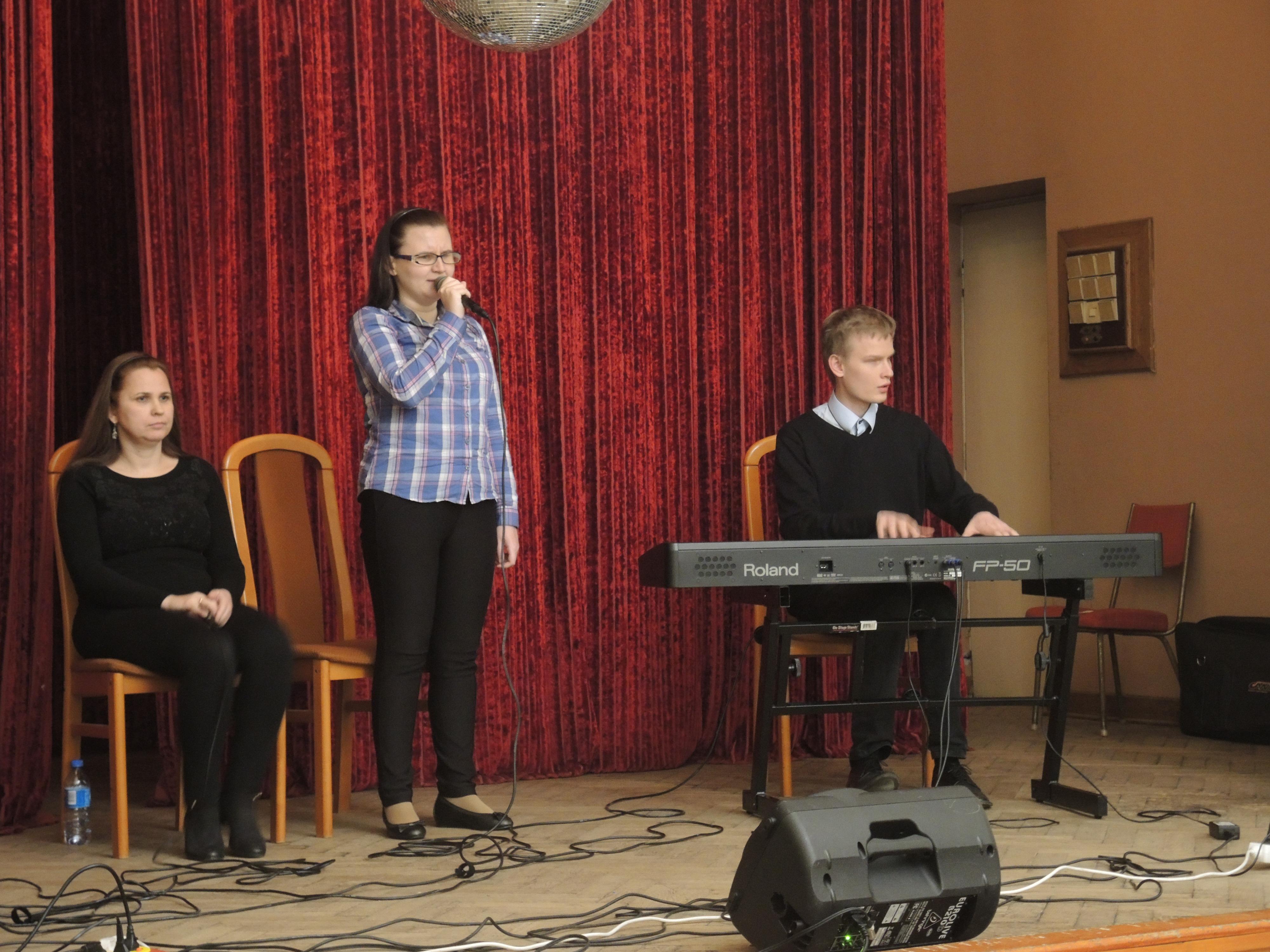 Na zdjęciu znajdują się trzy osoby. Mężczyzna gra na klawiszach, a po jego prawej stronie znajdują się dwie kobiety. Jedna stoi, śpiewa, a druga siedzi na krześle.