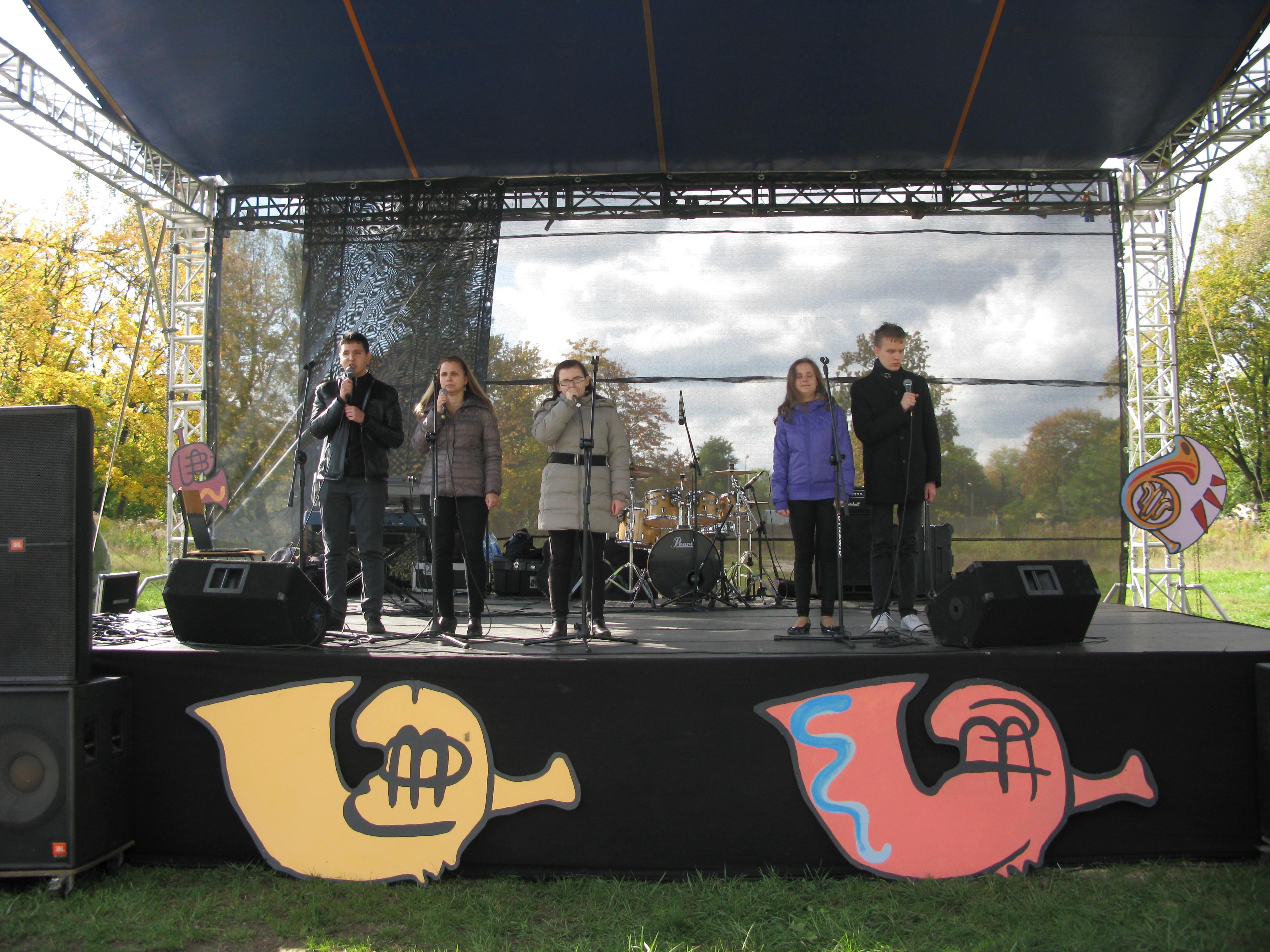 Na scenie stoi  5 osób. Trzy kobiety i dwóch mężczyzn. W dłoniach trzymają mikrofony.