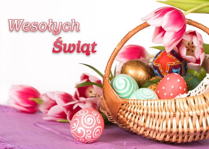 Koszyk wypełniony kolorowymi pisankami. W tle widać kilka różowo-białych tulipanów. Na białym tle, tuż obok koszyka, widnieje napis: Wesołych Świąt.