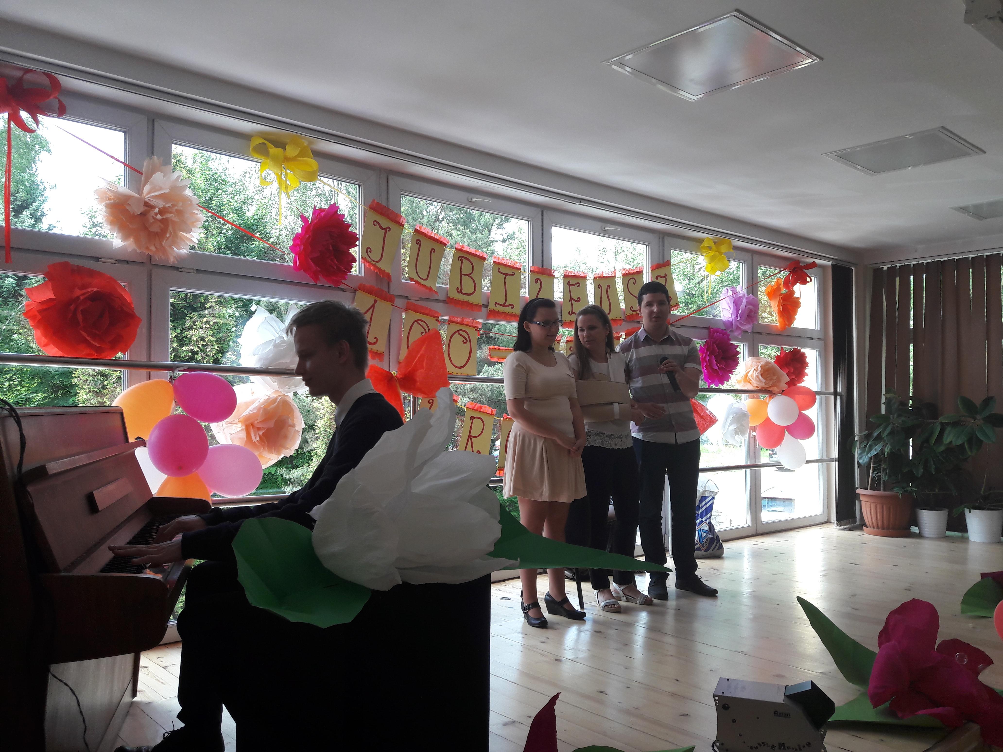 Na scenie znajdują się cztery osoby. Dwie kobiety i dwóch mężczyzn. Jeden stoi, w ręce trzyma mikrofon, obok niego stoją kobiety. Drugi gra na pianinie.