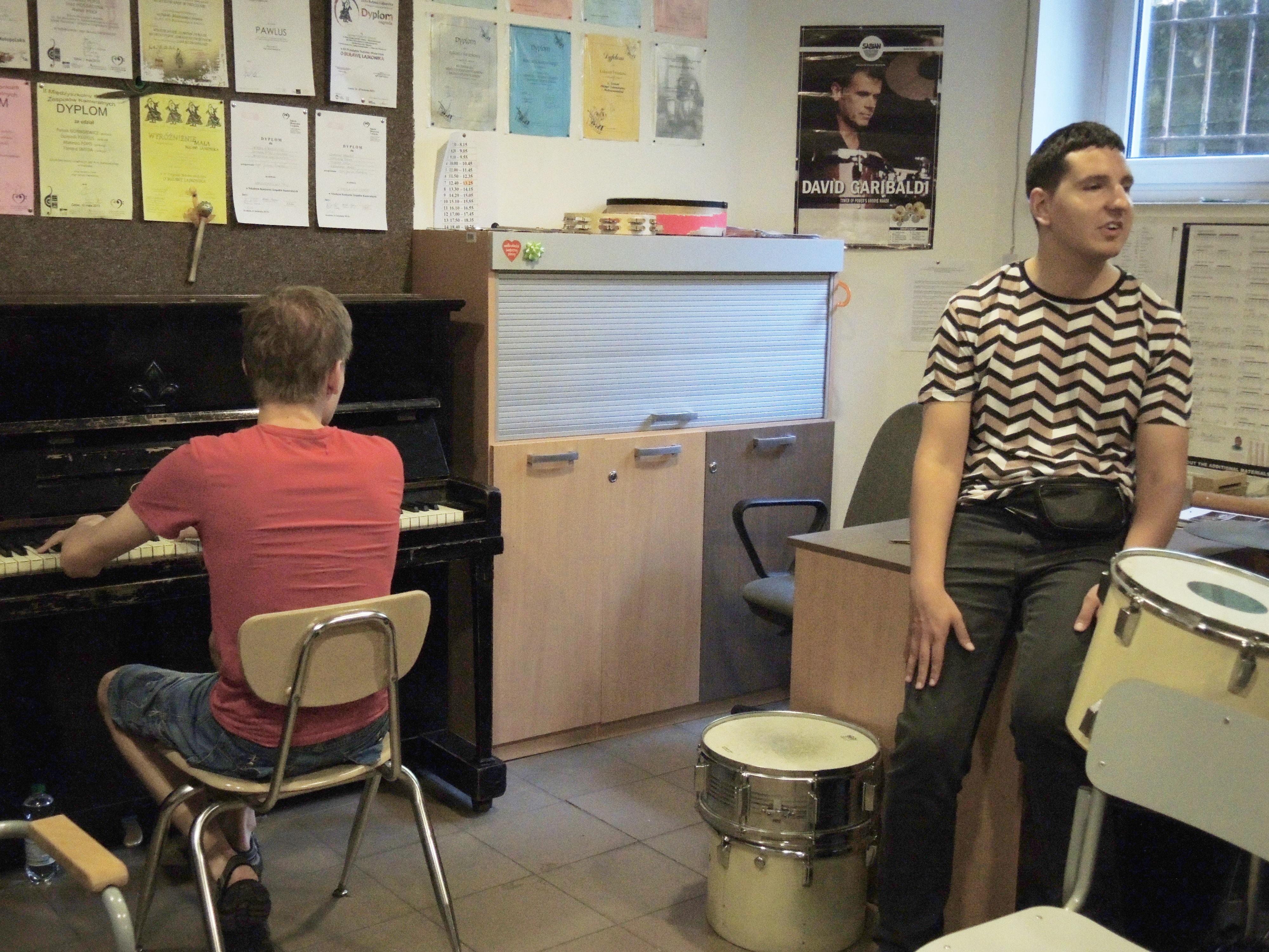 Na zdjęciu znajduje się dwóch mężczyzn. Jeden siedzi na krawędzi biurka, a drugi gra na fortepianie.
