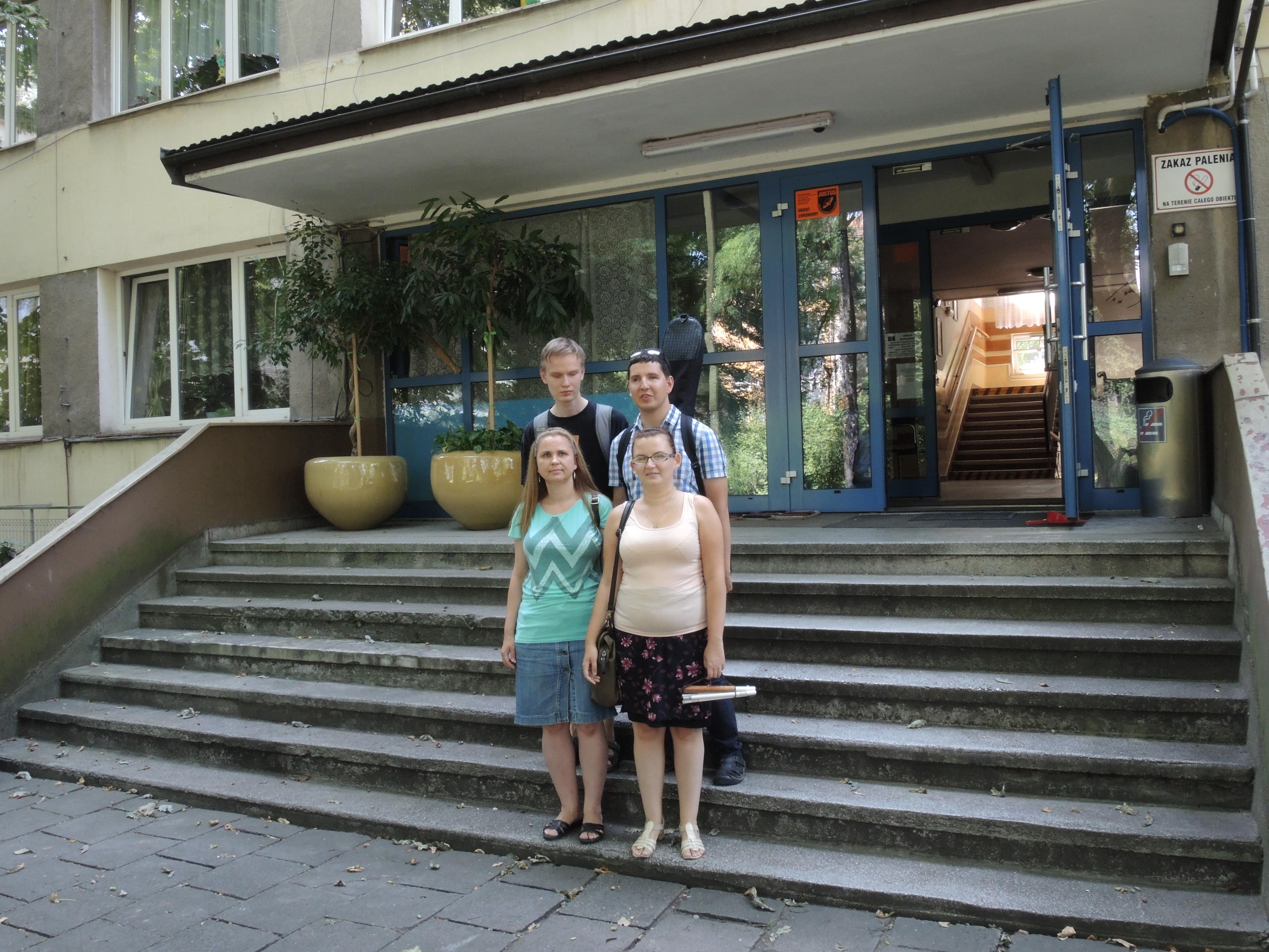 Cztery osoby - dwie kobiety i dwóch mężczyzn - stoją na schodach przed budynkiem.