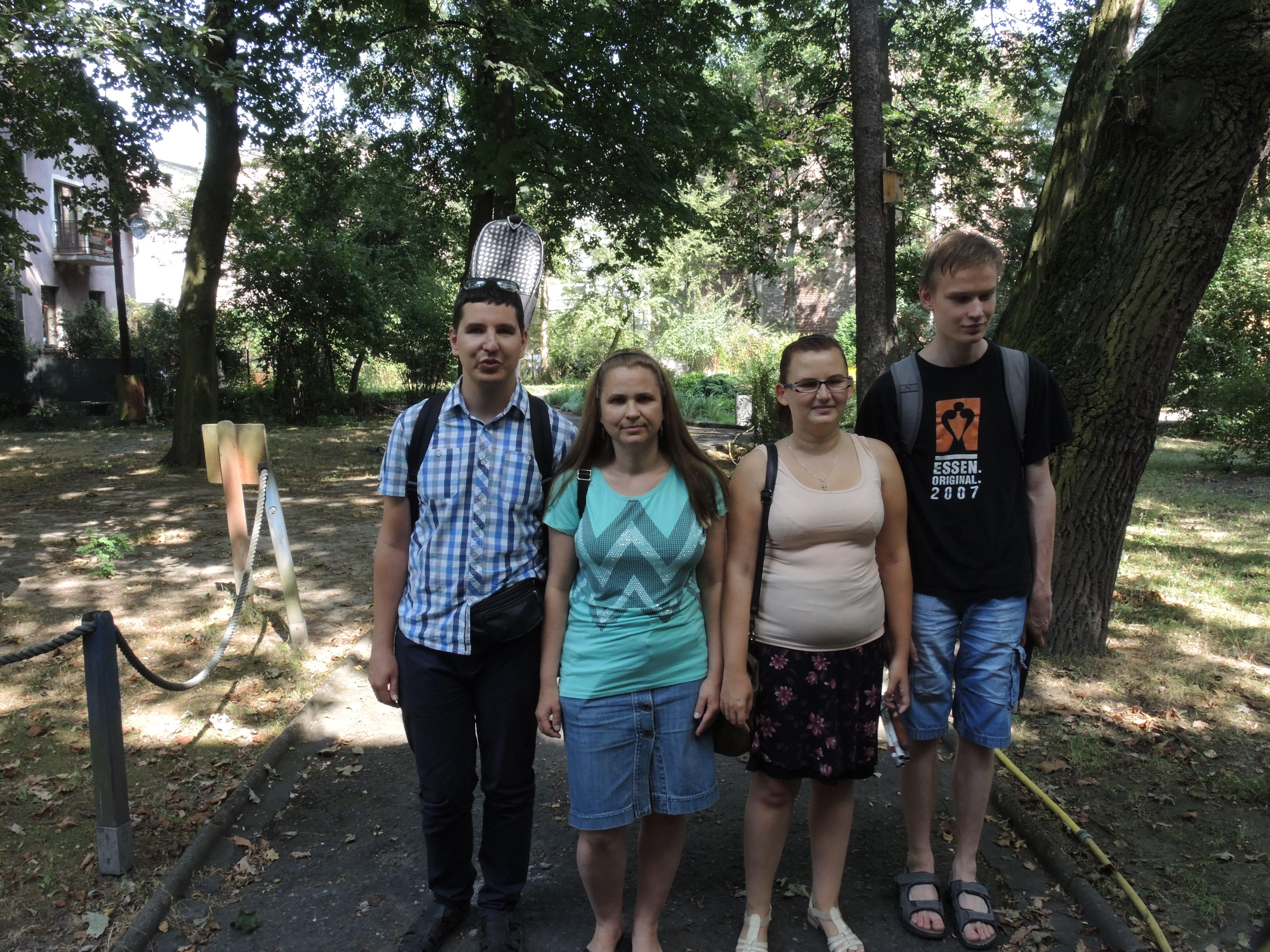 Cztery osoby stoją na chodniku. W tle widać drzewa.