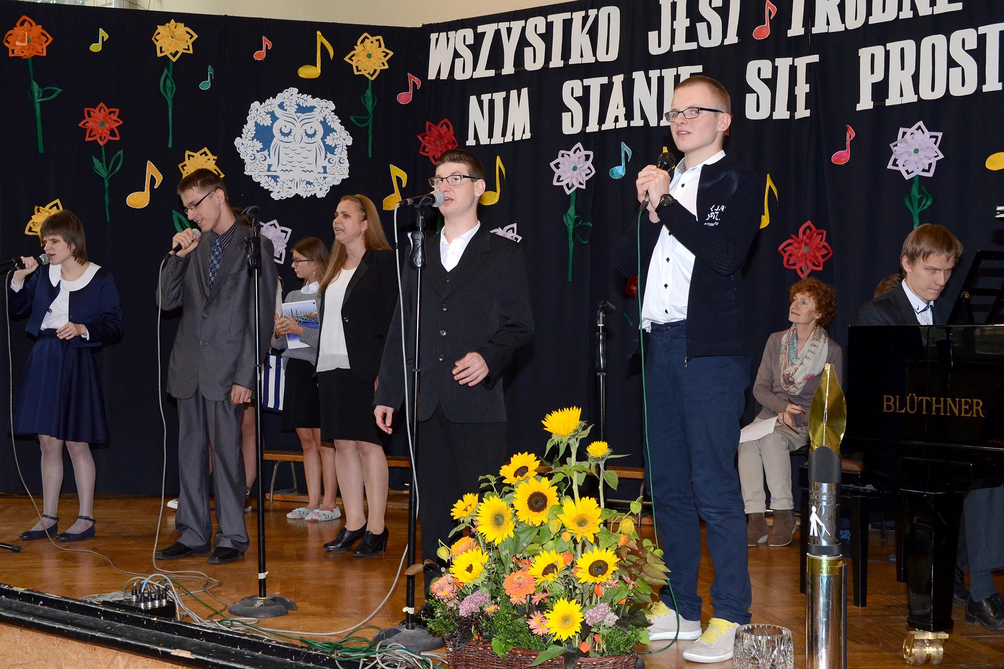 Kadr z artystycznej części akademii. Na scenie znajduje się osiem osób. Mężczyzna gra na fotepianie, sześć osób stoi, za nimi siedzi kobieta.