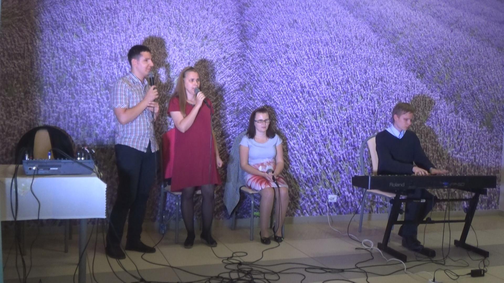 Dwoje ludzi stoi na scenie - kobieta i mężyzna. Obok nich, na krześle, siedzi kobieta, która w rękach trzyma mikrofon. Obok niej siedzi mężczyzna, który przed sobą ma klawisze.