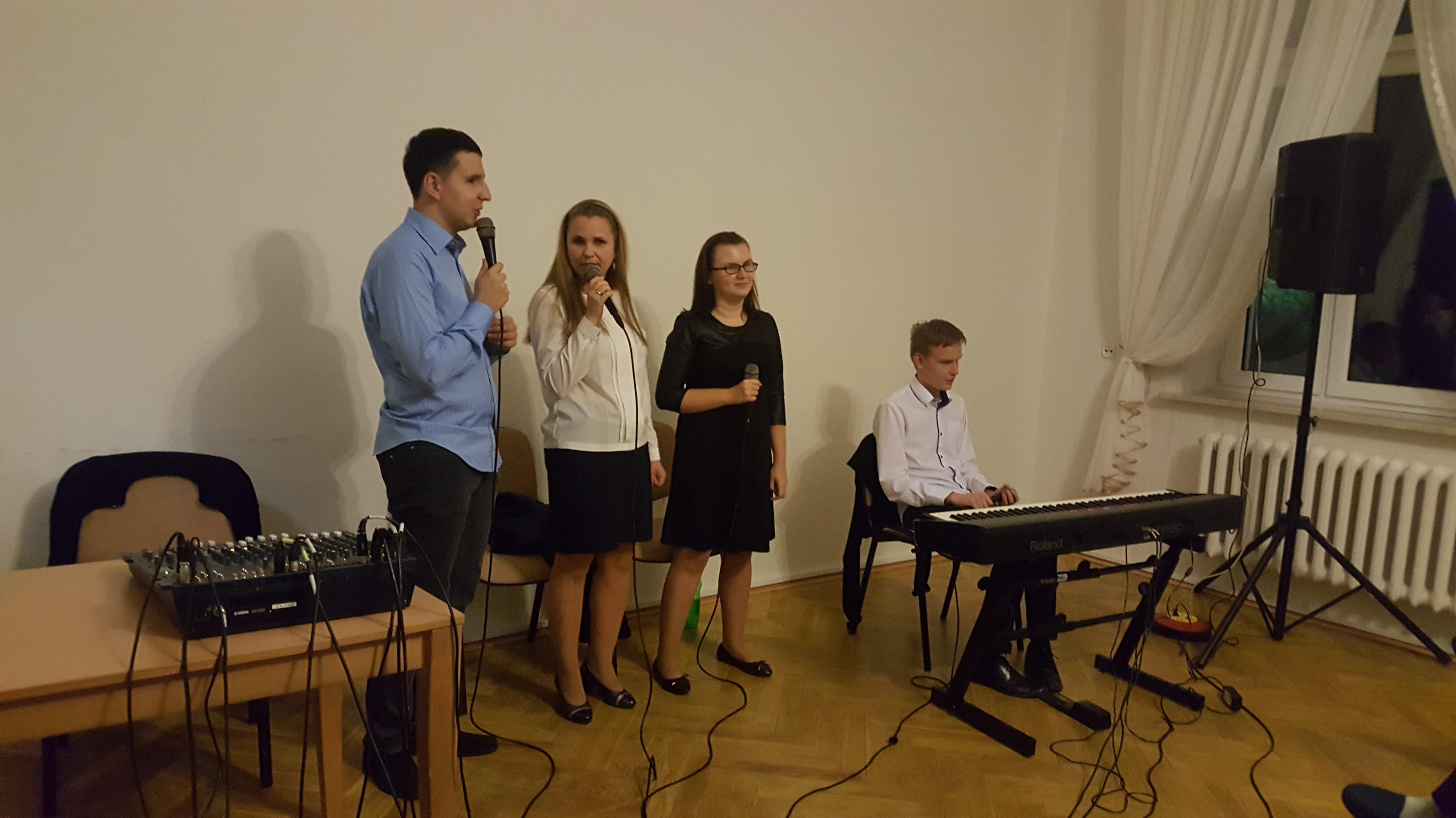 Trzy osoby stoją - jeden mężczyzna i dwie kobiety - w dłoniach trzymają mikrofony. Po ich lewej stronie siedzi mężczyzna, który przed sobą ma klawisze.
