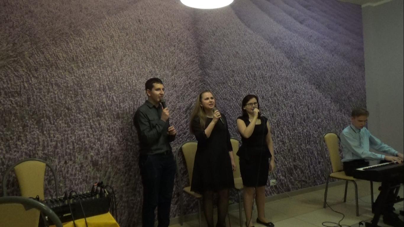 Trzy osoby stoją, (dwie kobiety i mężczyzna) śpiewają. Po ich lewej stronie drugi mężczyzna gra na pianinie elektycznym.