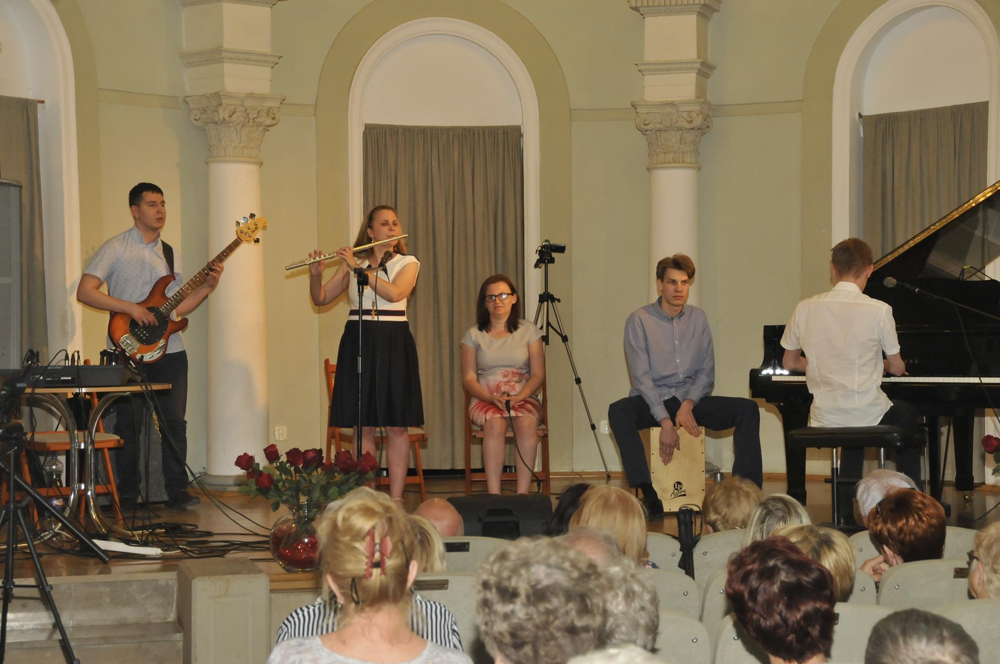 Kobieta gra na flecie poprzecznym. Po jej prawej stronie stoi mężczyzna, który gra na gitarze basowej, po lewej na krześle siedzi kobieta, która w dłoniach trzyma mikrofon, po jej lewej stronie mężczyzna gra na cahonie, obok niego mężczyzna gra na fortepianie.