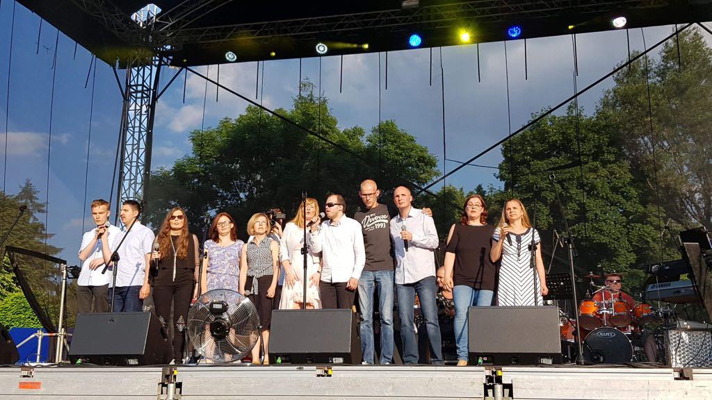 Jedenaście osób stoi na dużej scenie, za nimi zespół.