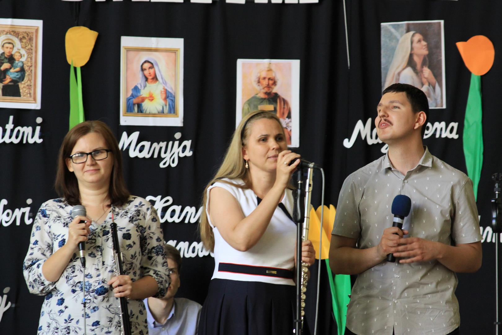 Kobieta sięga po mikrofon, który jest na statywie, w lewej dłoni trzyma flet poprzeczny. Po jej lewej stronie stoi mężczyzna, a po prawej kobieta. W dłoniach trzymają mikrofony. Za nimi siedzi mężczyzna, który gra na cajonie.