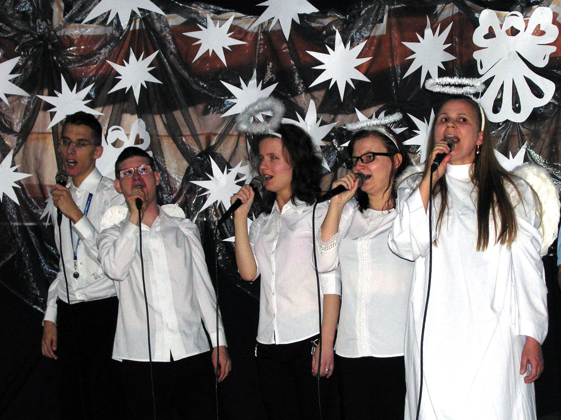 Na scenie śpiewa pięć osób (trzy kobiety, dwóch mężczyzn). Kobiety są przebrane za aniołki.