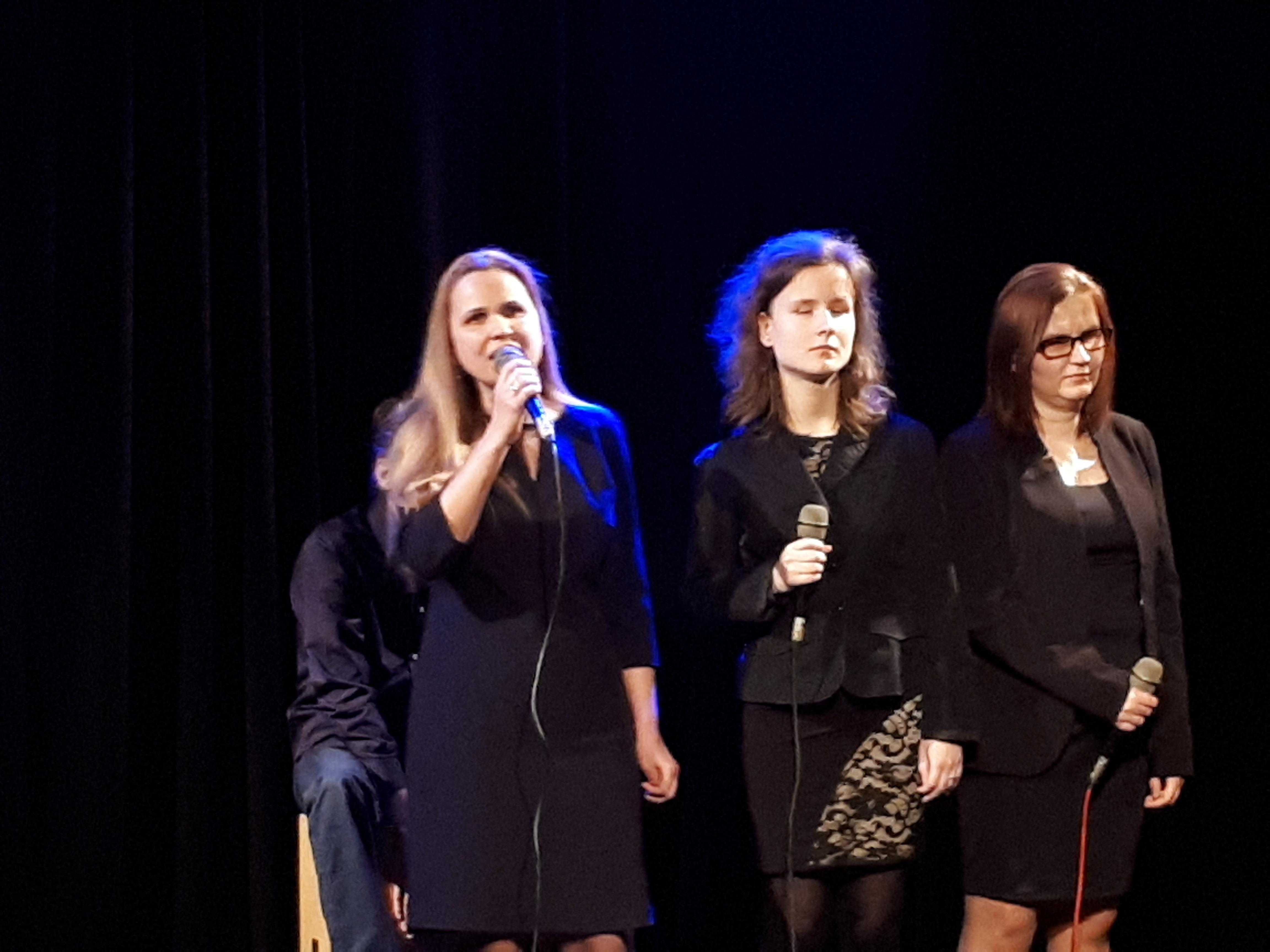 Trzy kobiety stoją, trzymają w rękach mikrofony. Jedna z nich śpiewa.