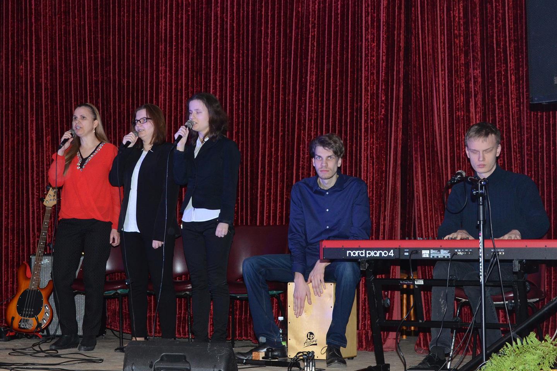 Trzy kobiety stoją, śpiewają. Obok nich dwóch mężczyzn - pierwszy gra na cajonie, drugi na pianinie elektrycznym.