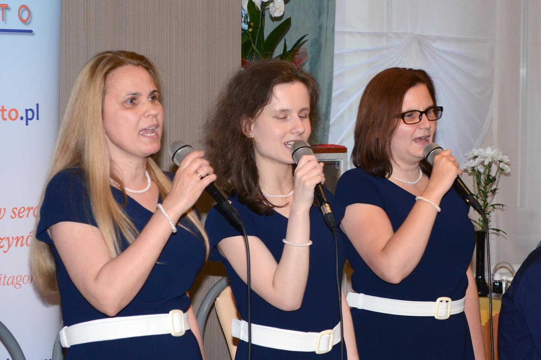 Trzy kobiety ubrane w sukienki stoją i śpiewają.