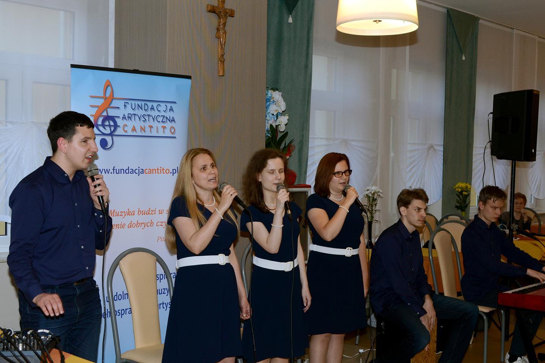 Cztery osoby (1 mężczyzna, 3 kobiety) stoją, śpiewają, pozostali (dwóch mężczyzn) gra na cajonie i pianinie elektycznym