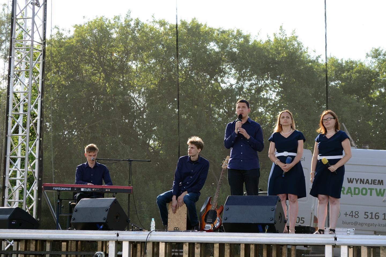 Mężczyzna śpiewa, obok niego stoją dwie kobiety. Po jego lewej stronie dwóch mężczyzn grających na instrumentach. Cajonie i pianinie elektycznym.