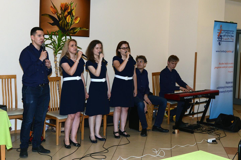 Cztery osoby (jeden mężczyzna, trzy kobiety) śpiewają. Obok nich dwóch mężczyzn gra na instrumentach. Jeden na cajonie, a drugi na pianinie elektrycznym.