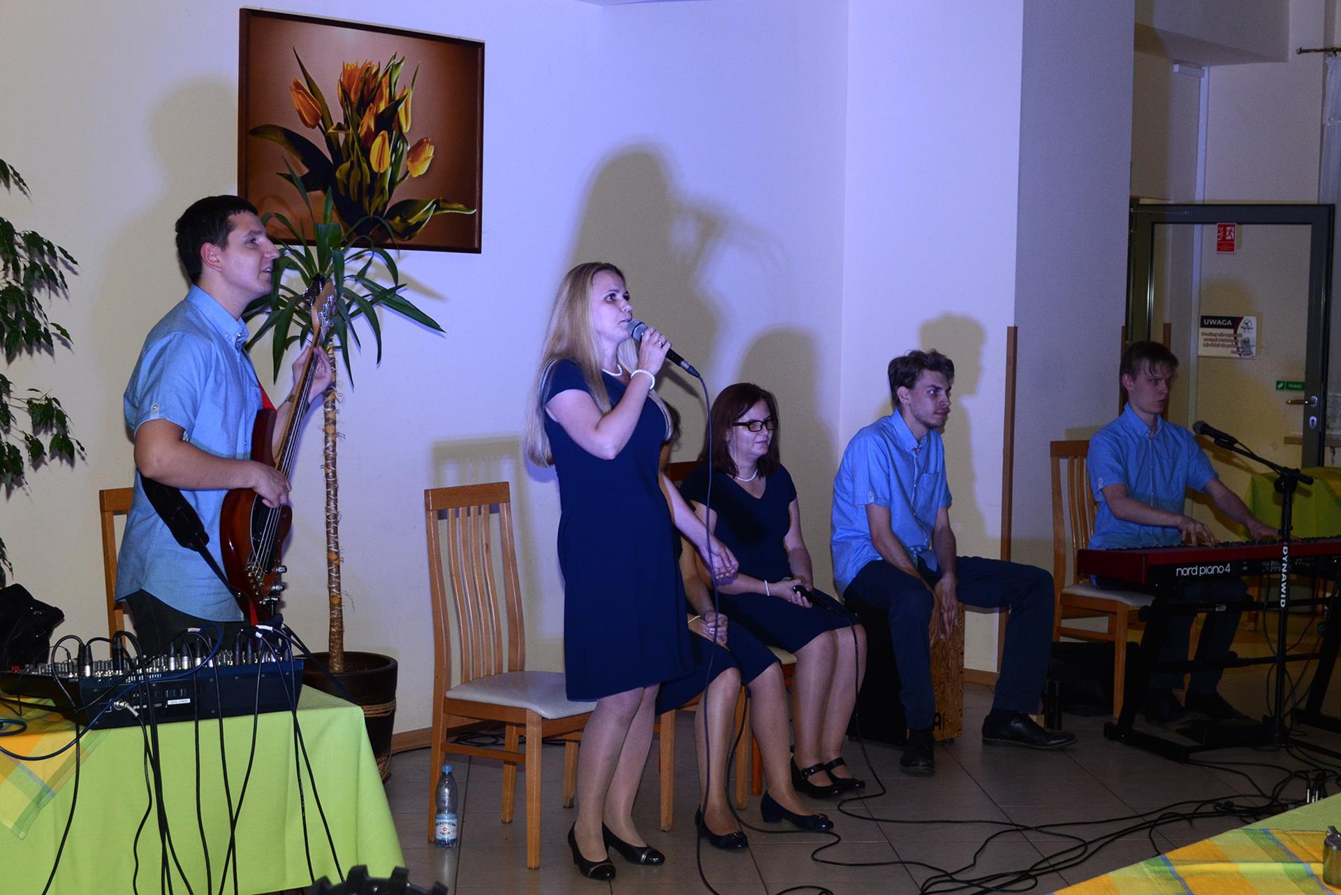 Na zdjęciu znajduje się 6 osób. Trzy kobiety (jedna śpiewa, pozostałe siedzą na krzesłach) oraz trzech mężczyzn. Pierwszy gra na gitarze basowej, drugi na cajonie, a trzeci na pianinie elektrycznym.
