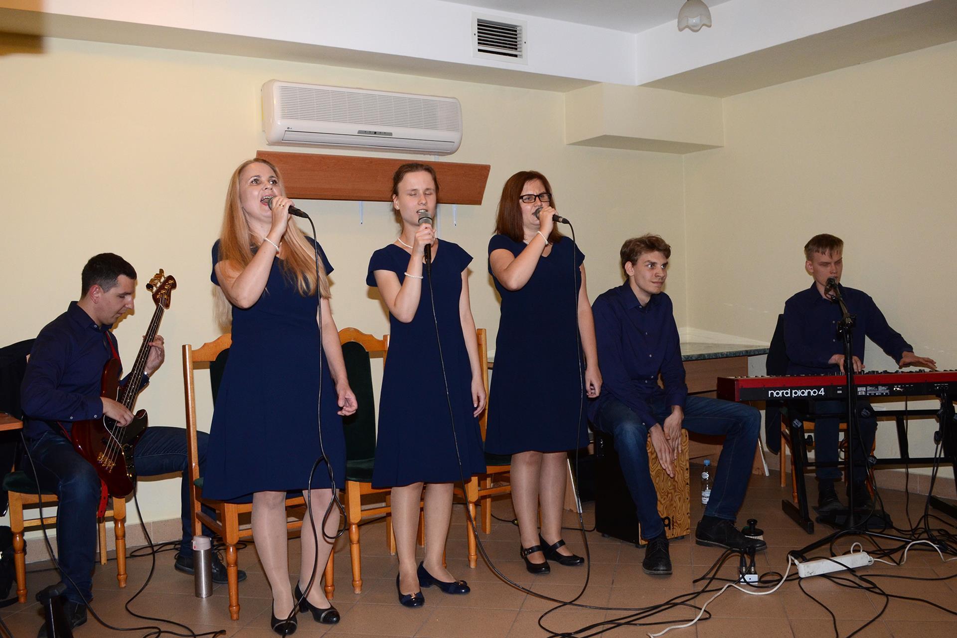 Mężczyzna siedzi, gra na basie. Trzy kobiety stoją, śpiewają. Obok, po ich lewej stronie, drugi mężczyzna gra na cajonie, a trzeci na pianinie elektrycznym.